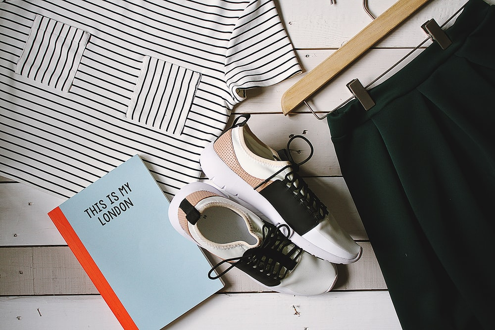 pair of white-and-black low-top sneakers near black skirt on brown clothes hanger top view photography