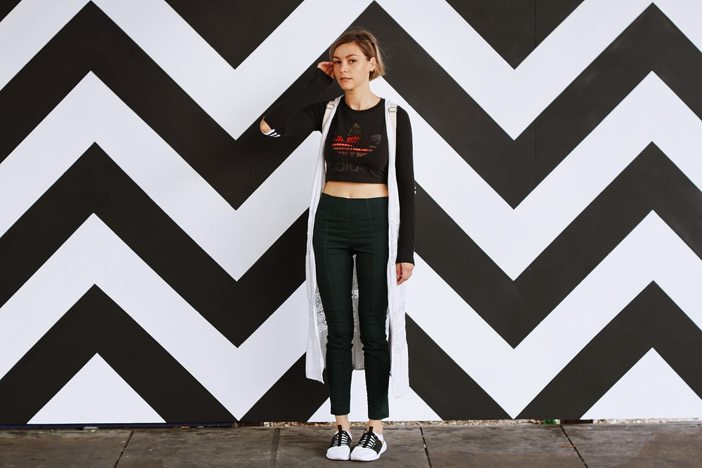 woman standing beside white and black chevron wall