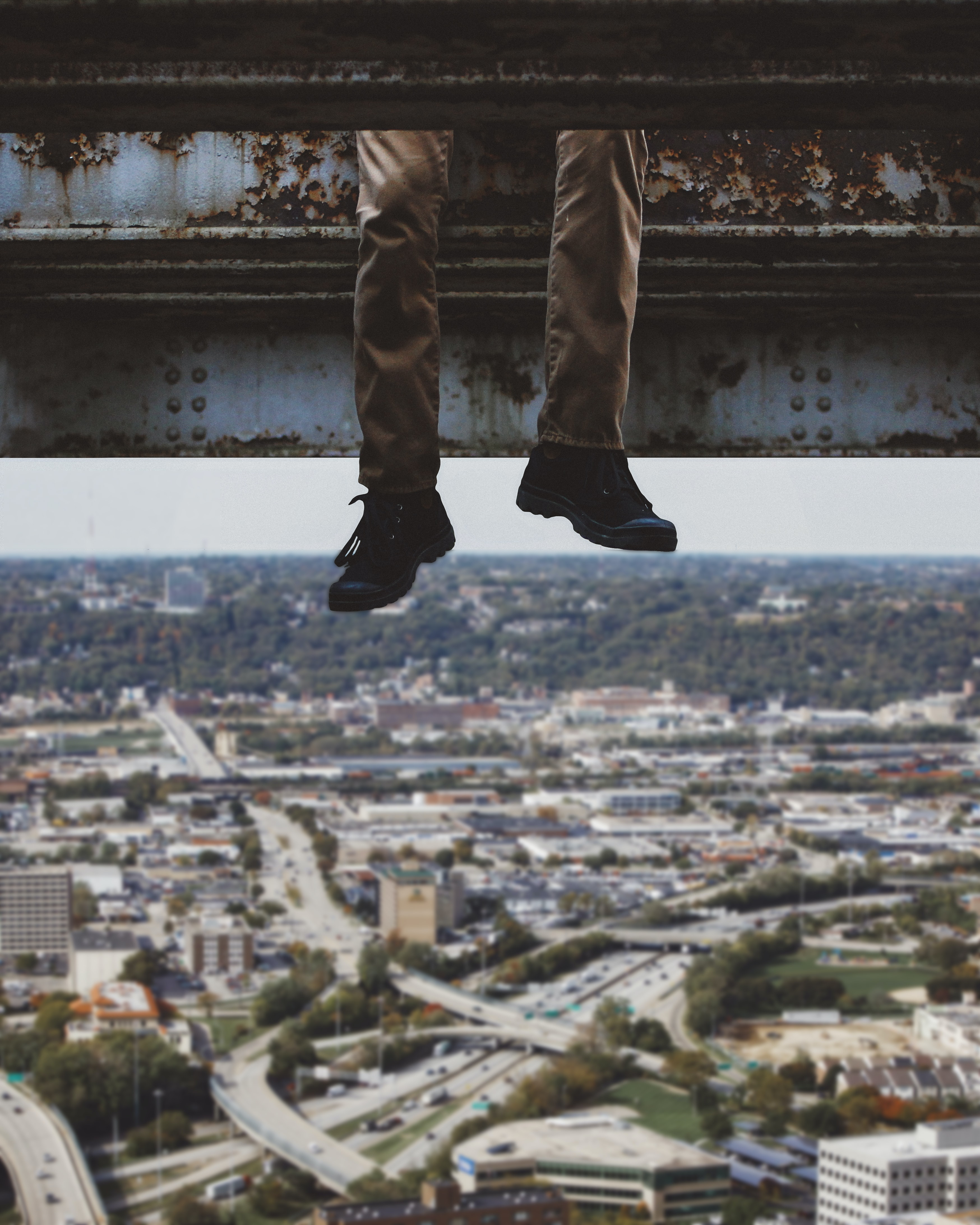 A guy sitting on a steel beam dangling his legs over the city of Cincinnati