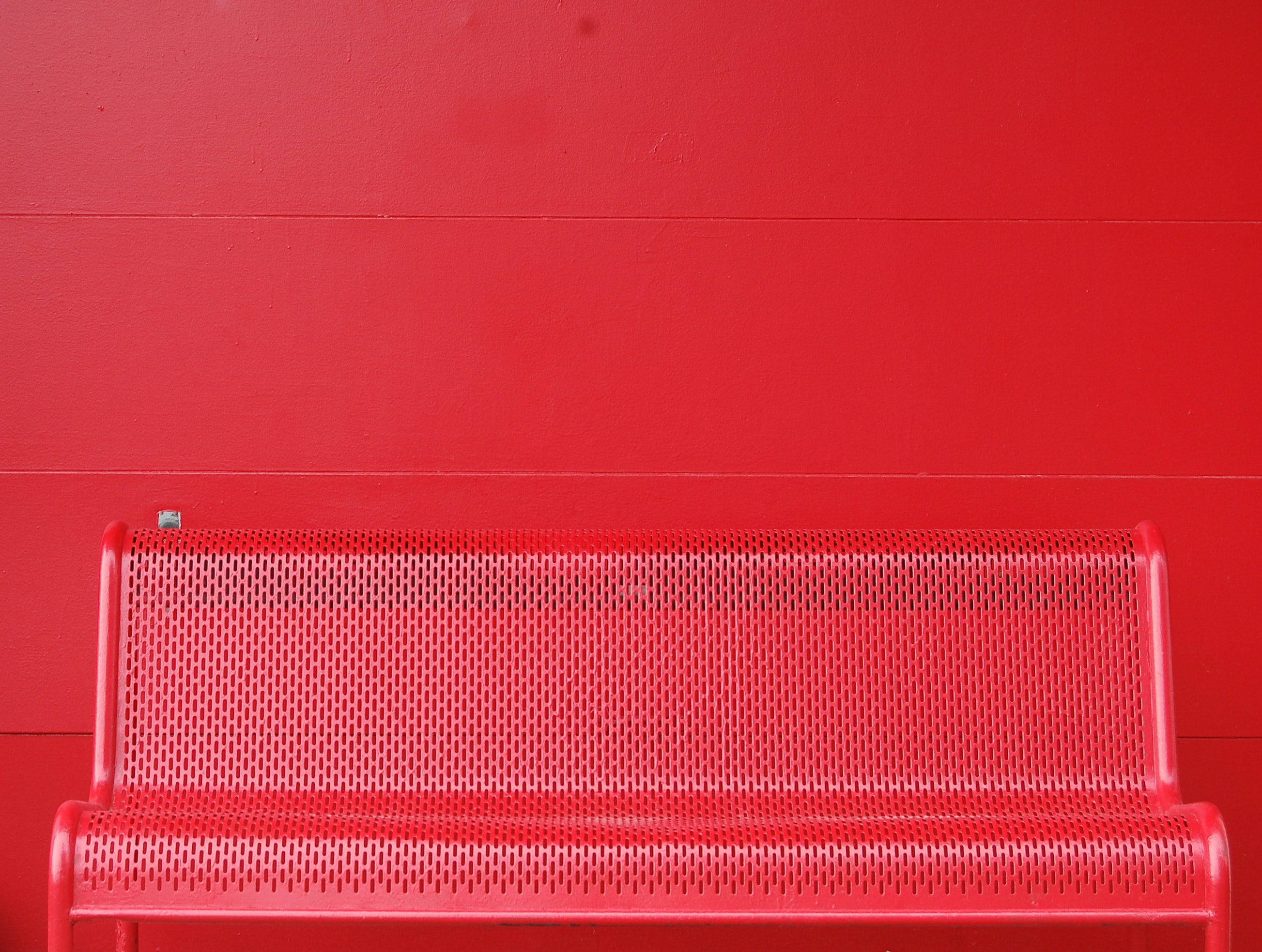 A red colored steel bench is attached to a red wall in Columbus.