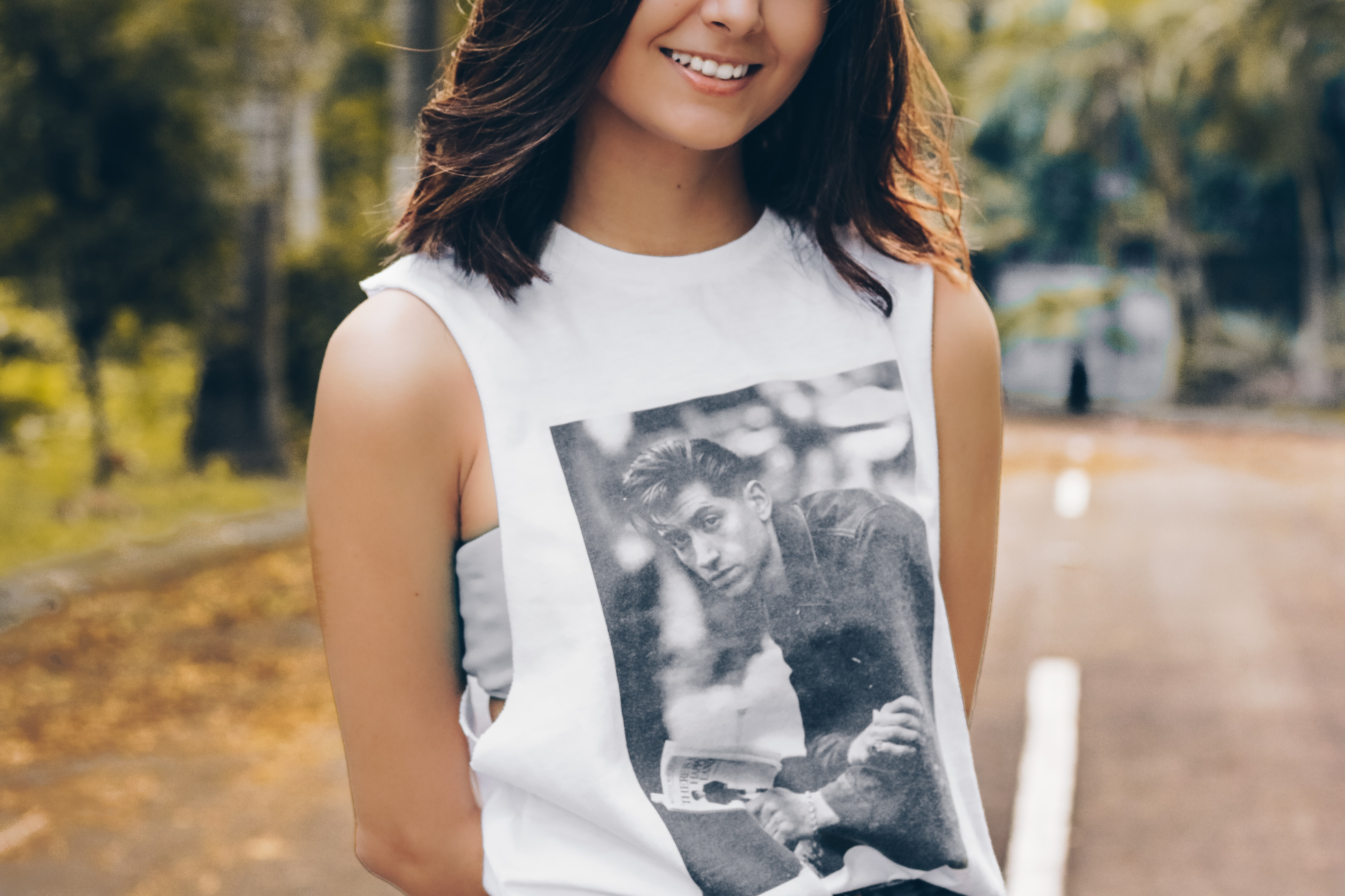 A smiling woman in an Arctic Monkeys tank top stands on a street by a park
