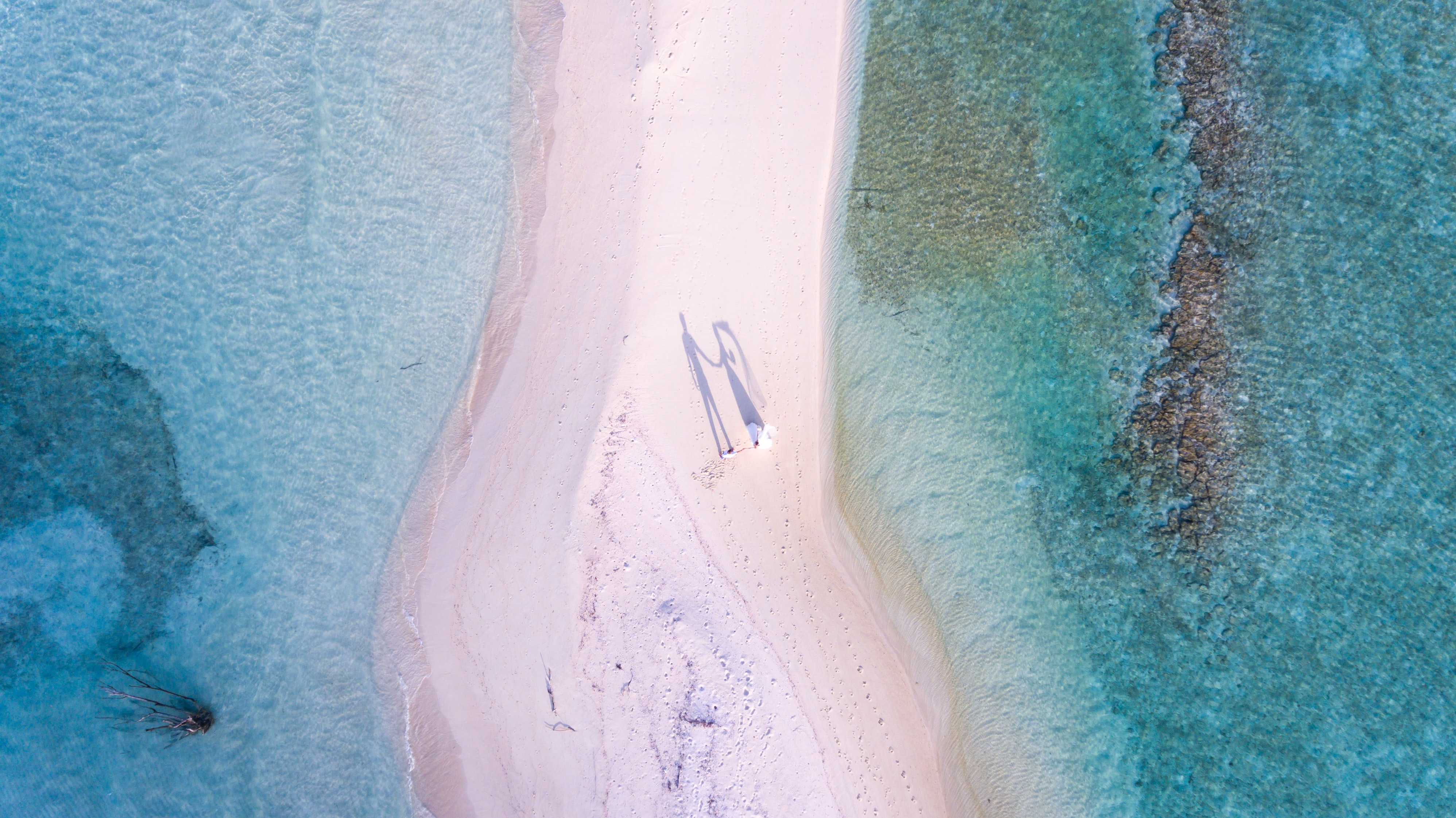 Drone aerial view of newly-wed couple on the sand beach stretch by the ocean at the North Central Province, Maldives