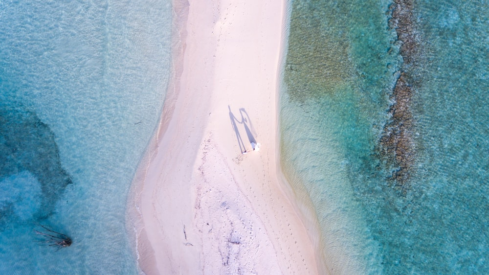 aerial photography of couple standing between body of water