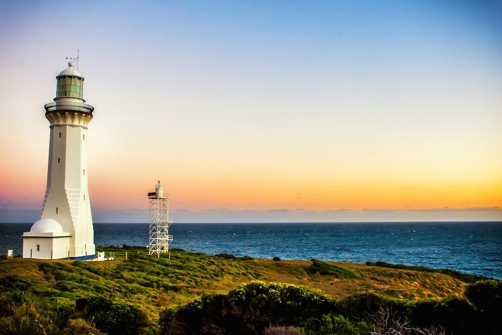 white concrete lighthouse near seashore at daytime