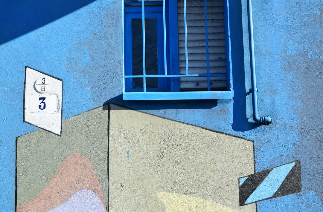 Urban building and window spray painted blue with graffiti sign and number 3