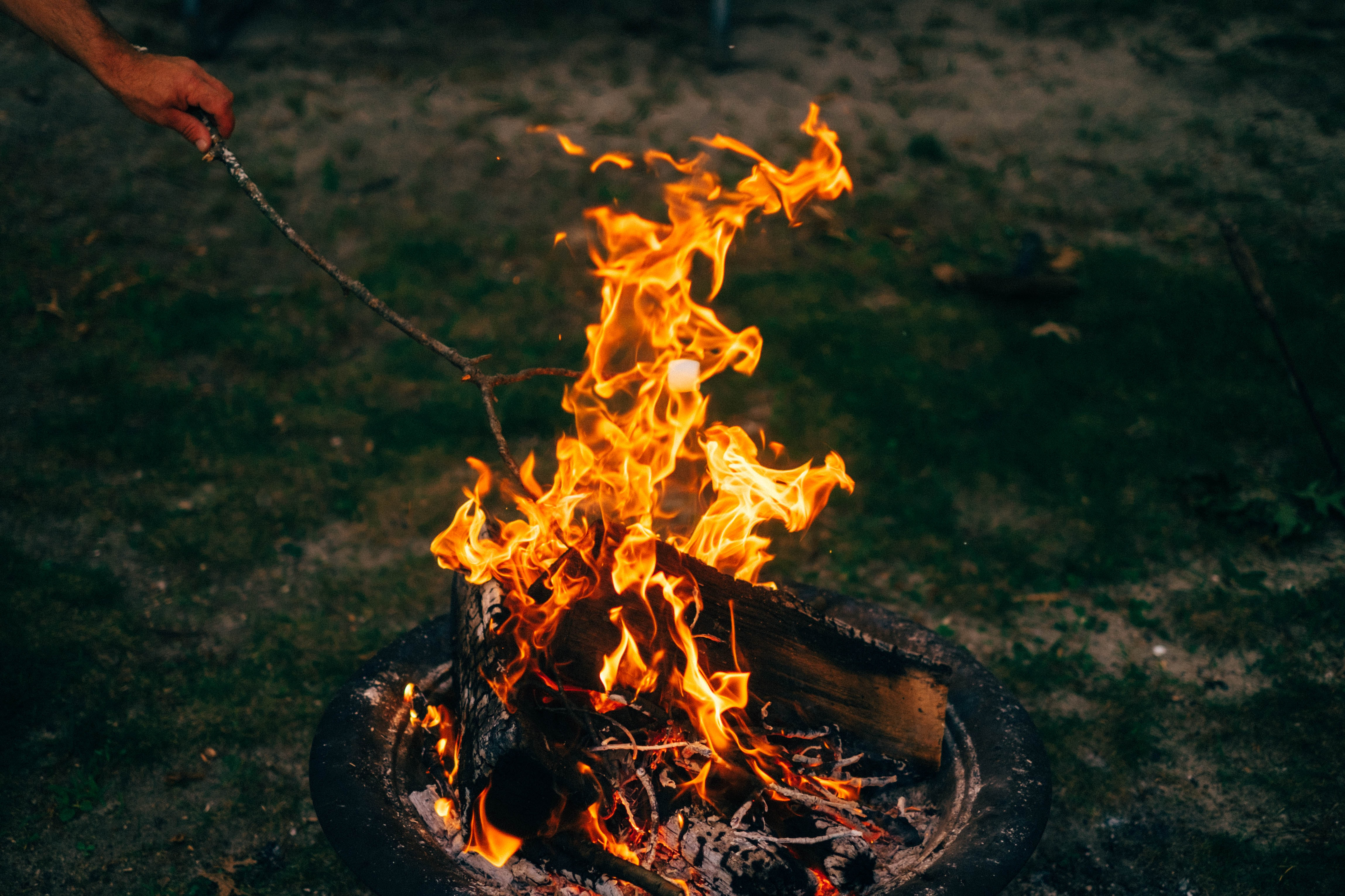 person burning twig on firepit