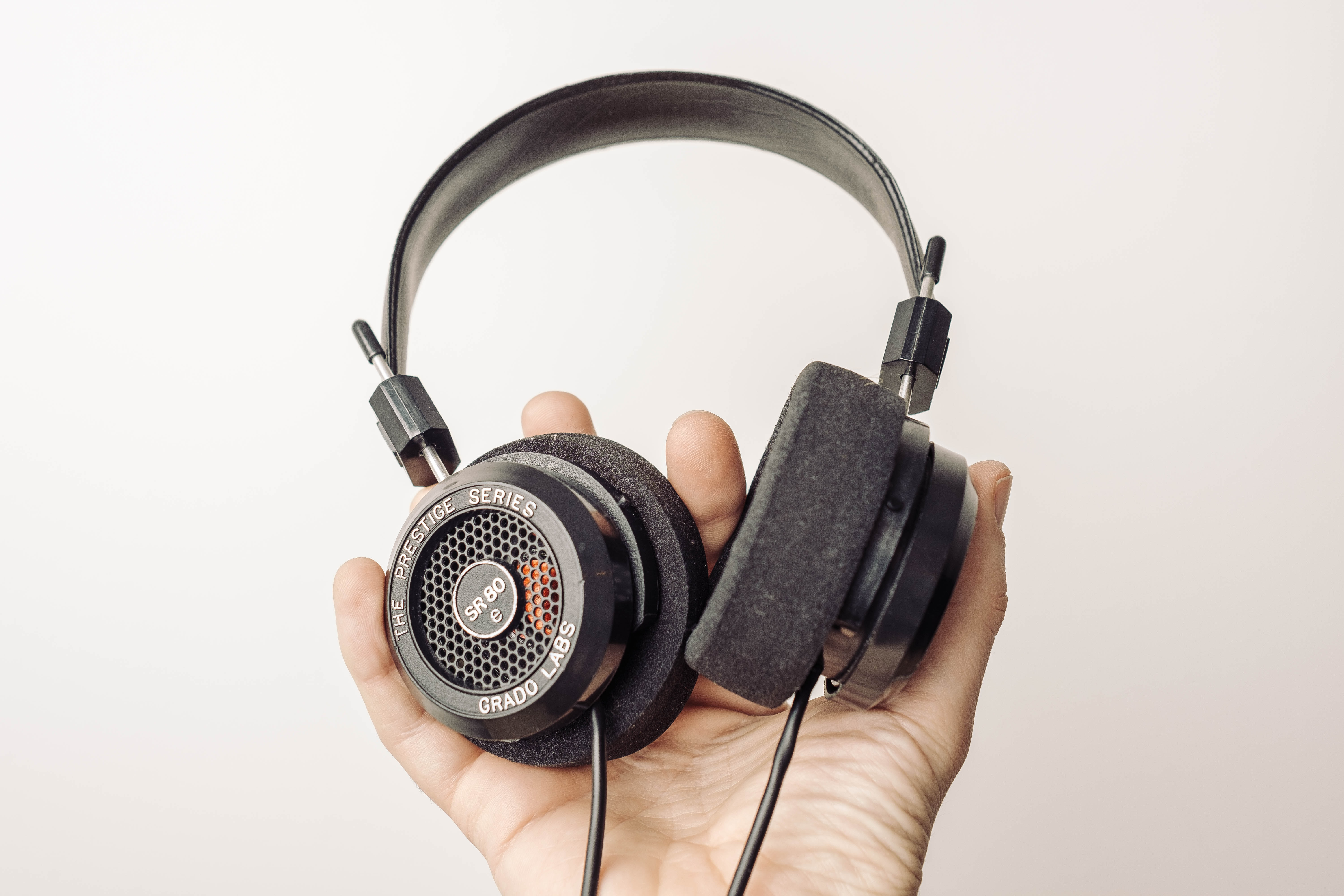 The Grado Headphones SR80e is held in a man's right hand.