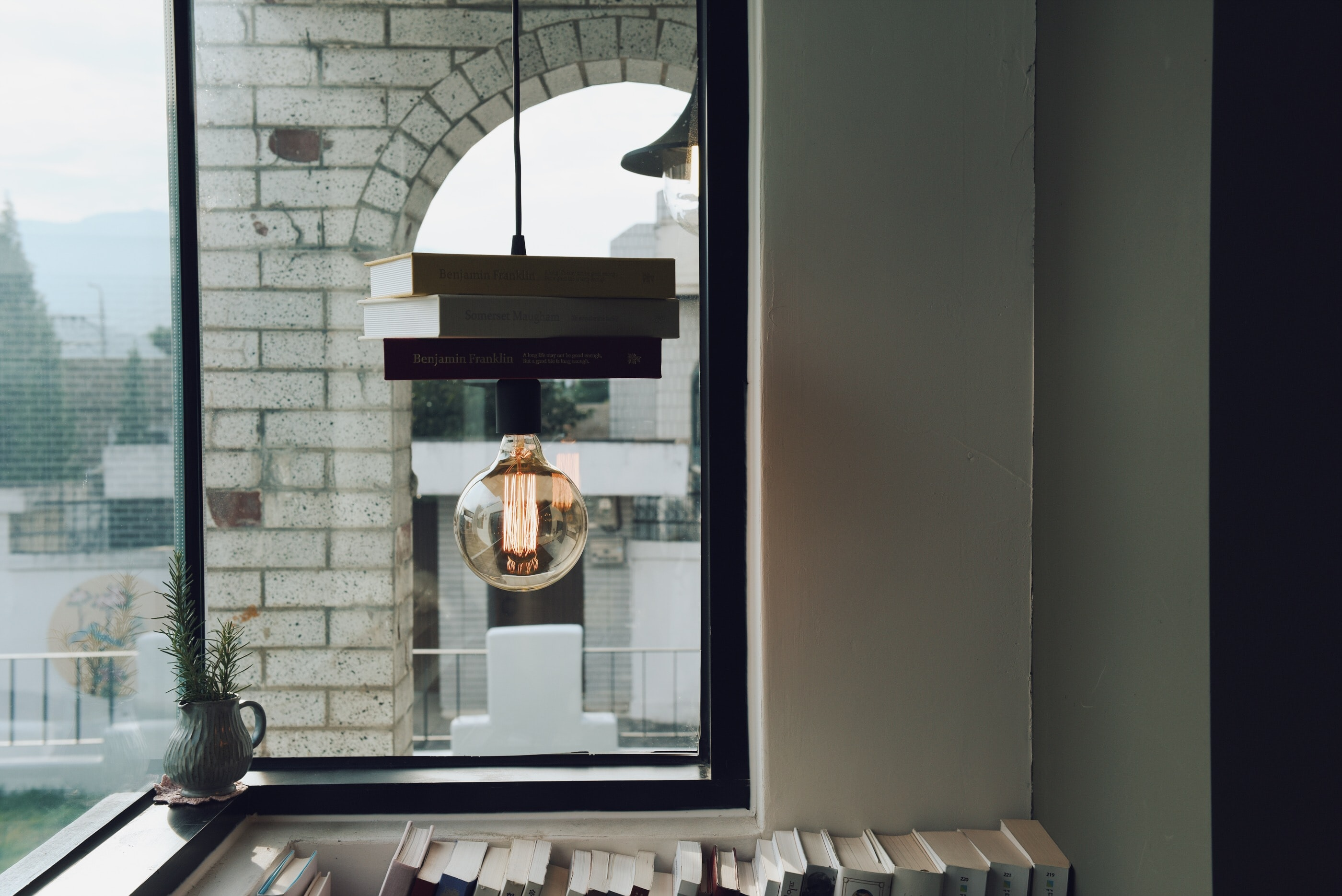 Lightbulb hangs from suspended books in a room with windows and a white brick building outside