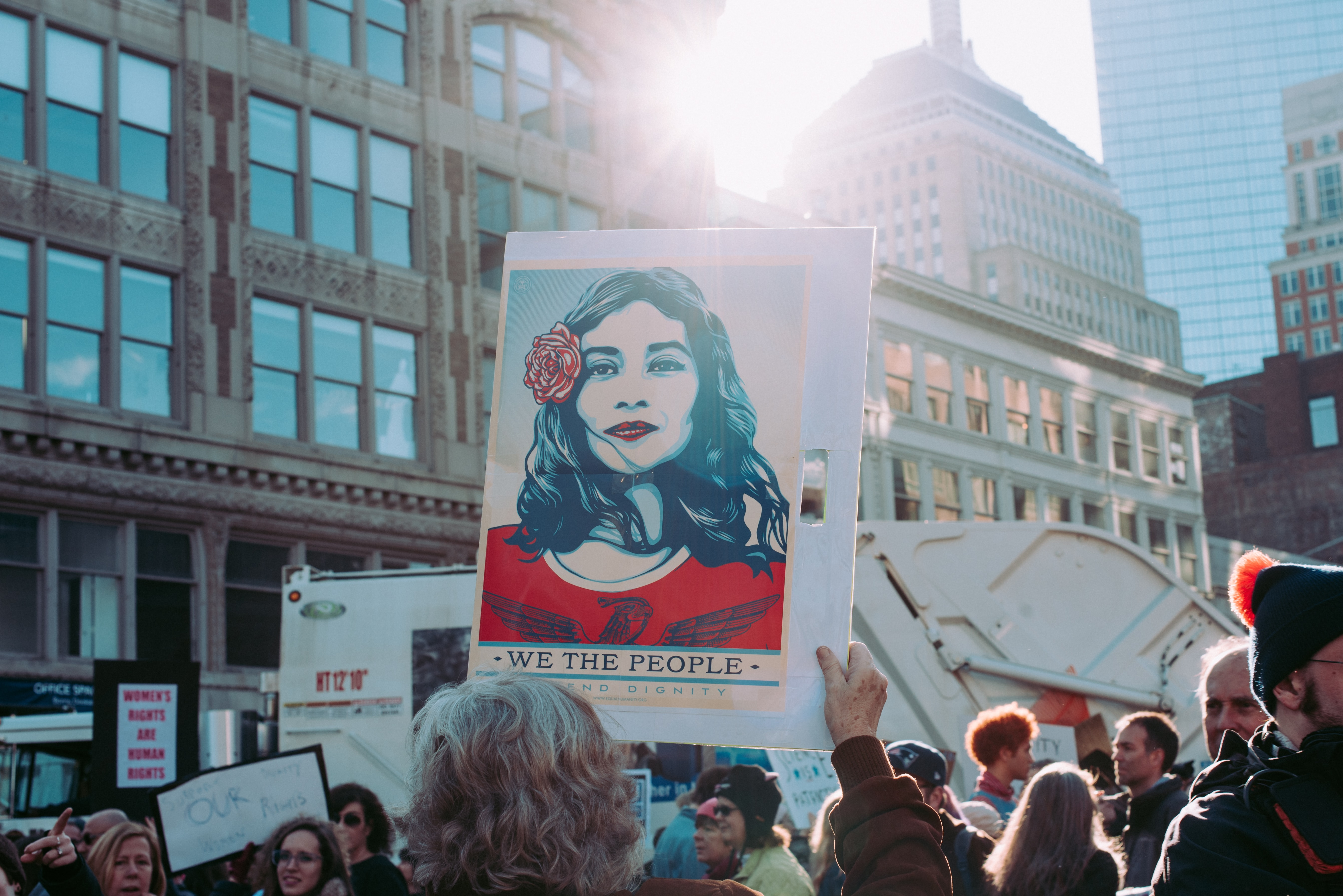 People hold up protest signs at the Women's March in Boston