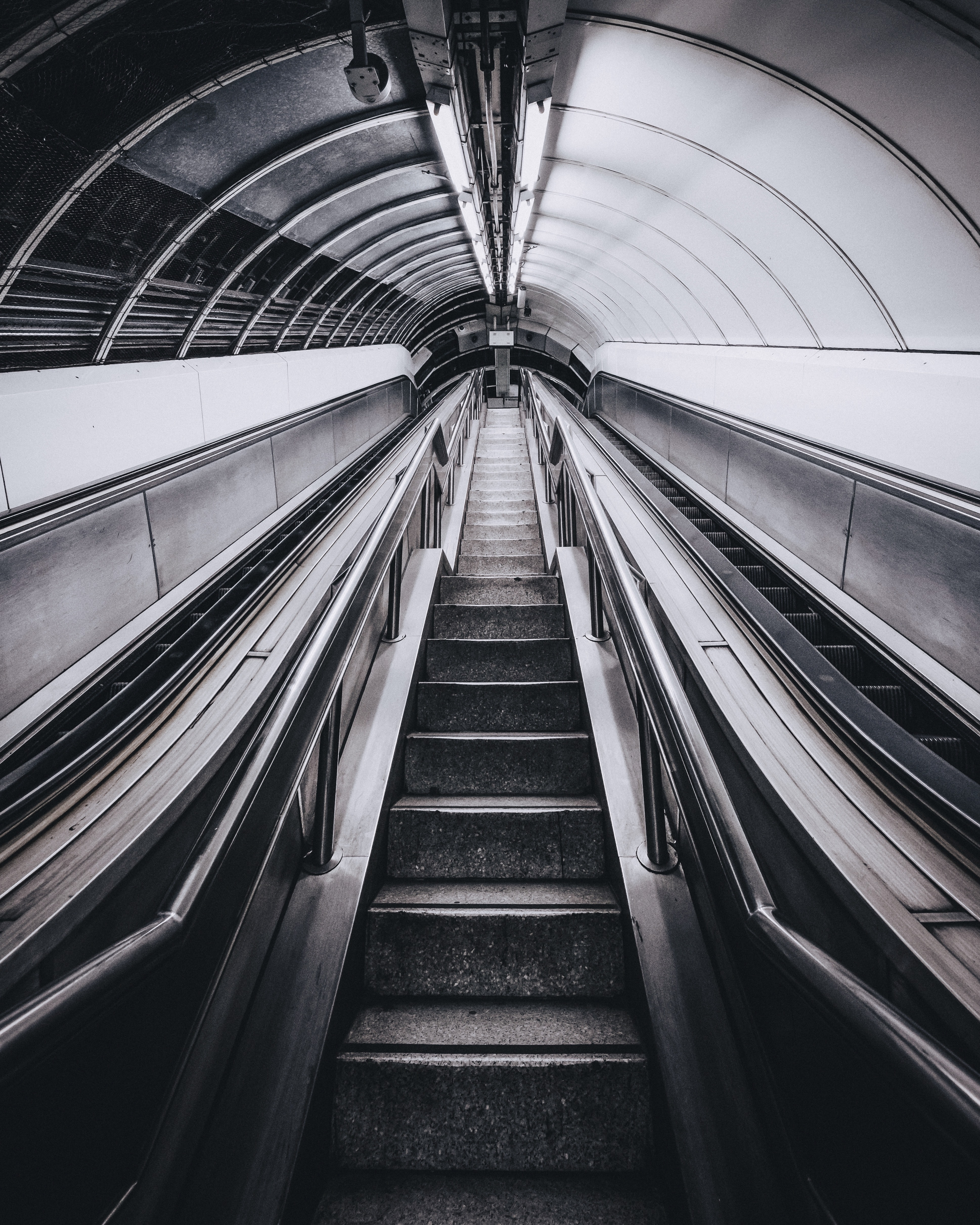 An empty staircase and two escalators in a tunnel in London
