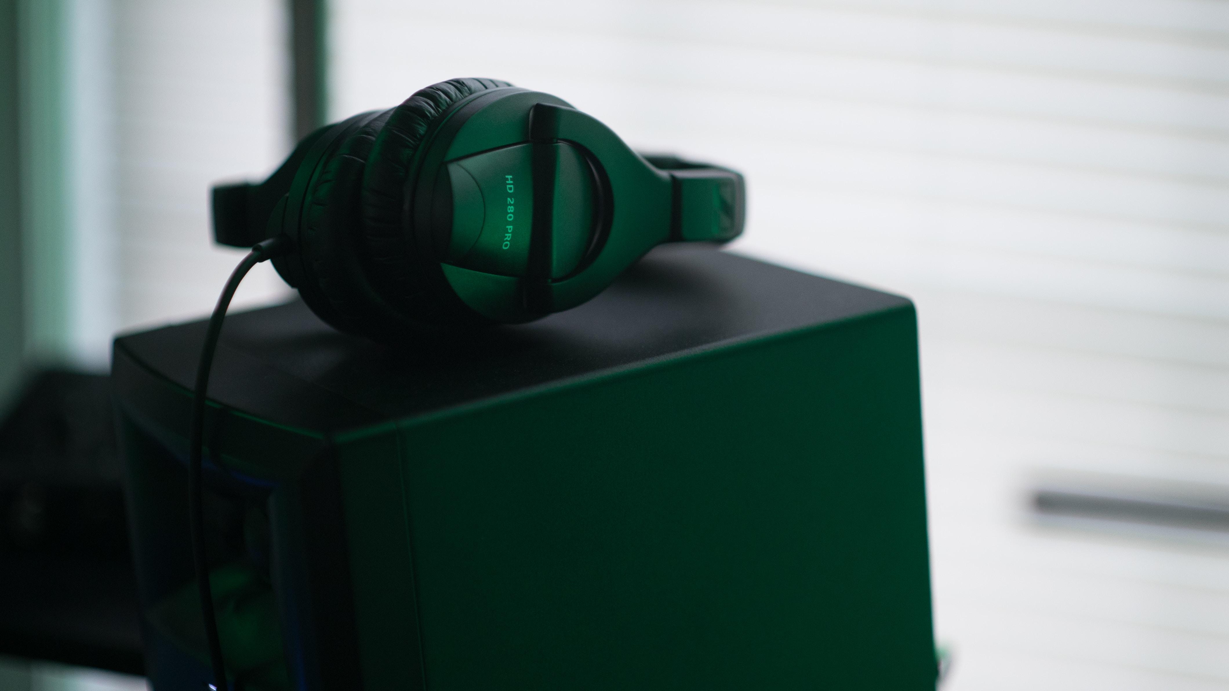 Headphones on top of a loudspeaker in dim green light