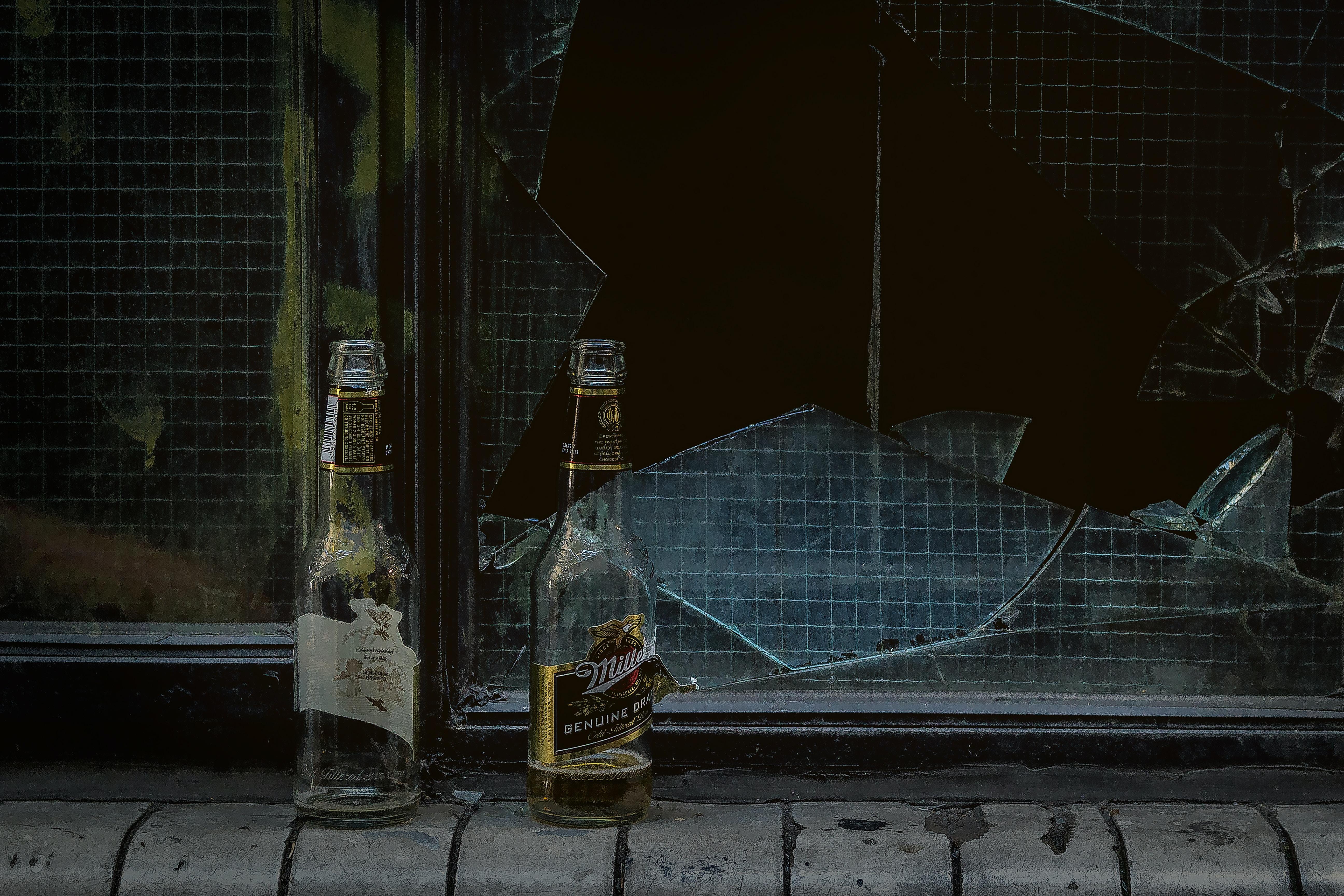 Two beer bottles in front of a broken glass window