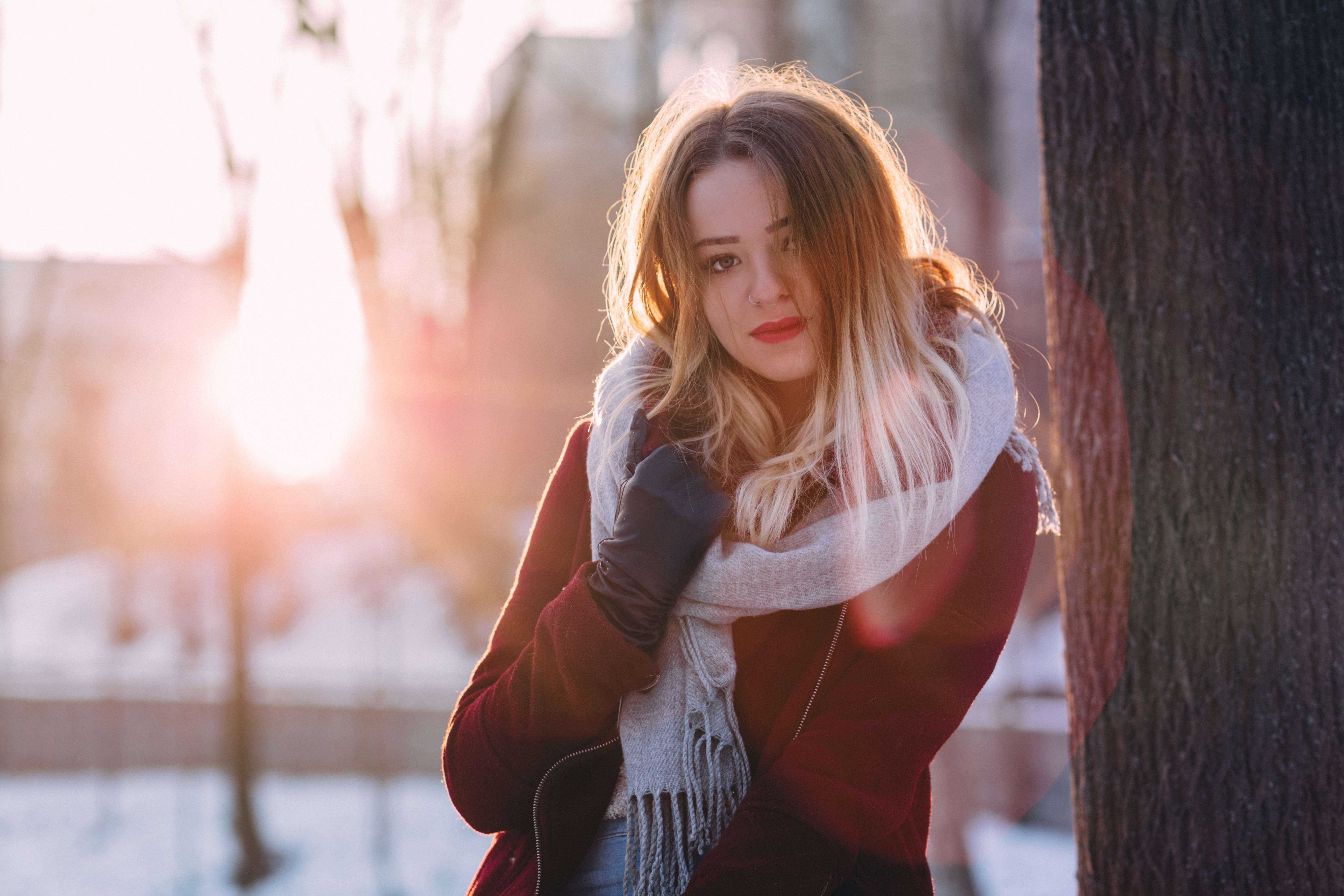 Woman in a winter sweater and fall scarf smiling near a tree outside