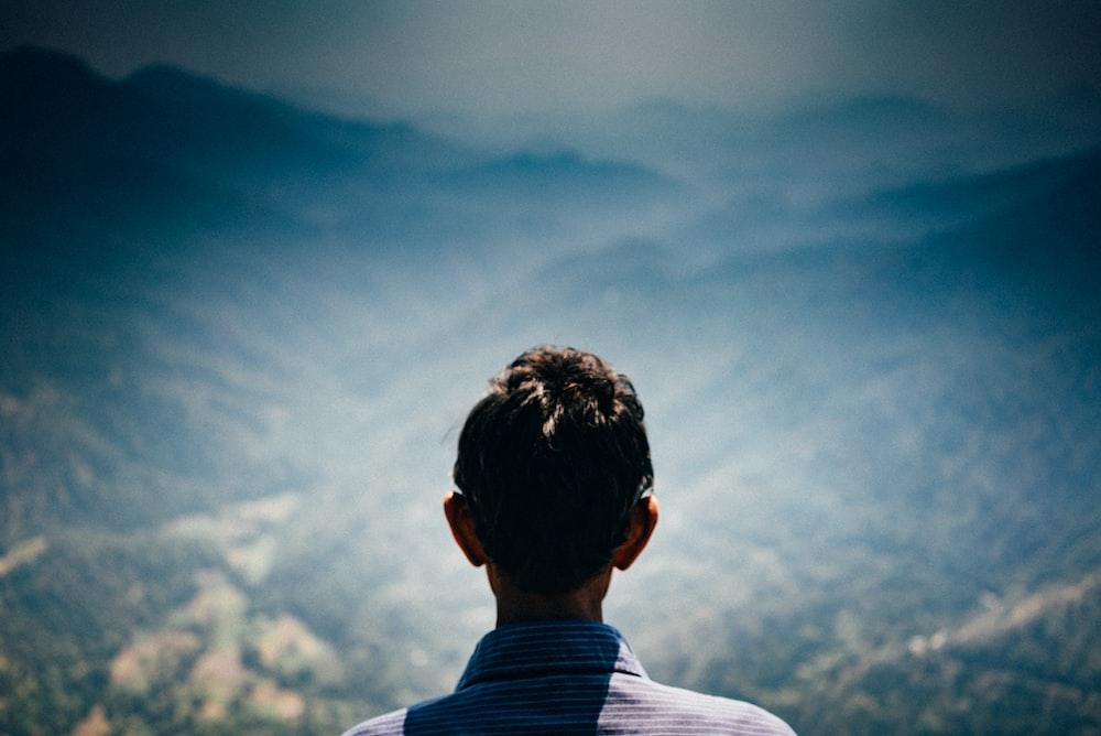 man facing green mountains during daytime