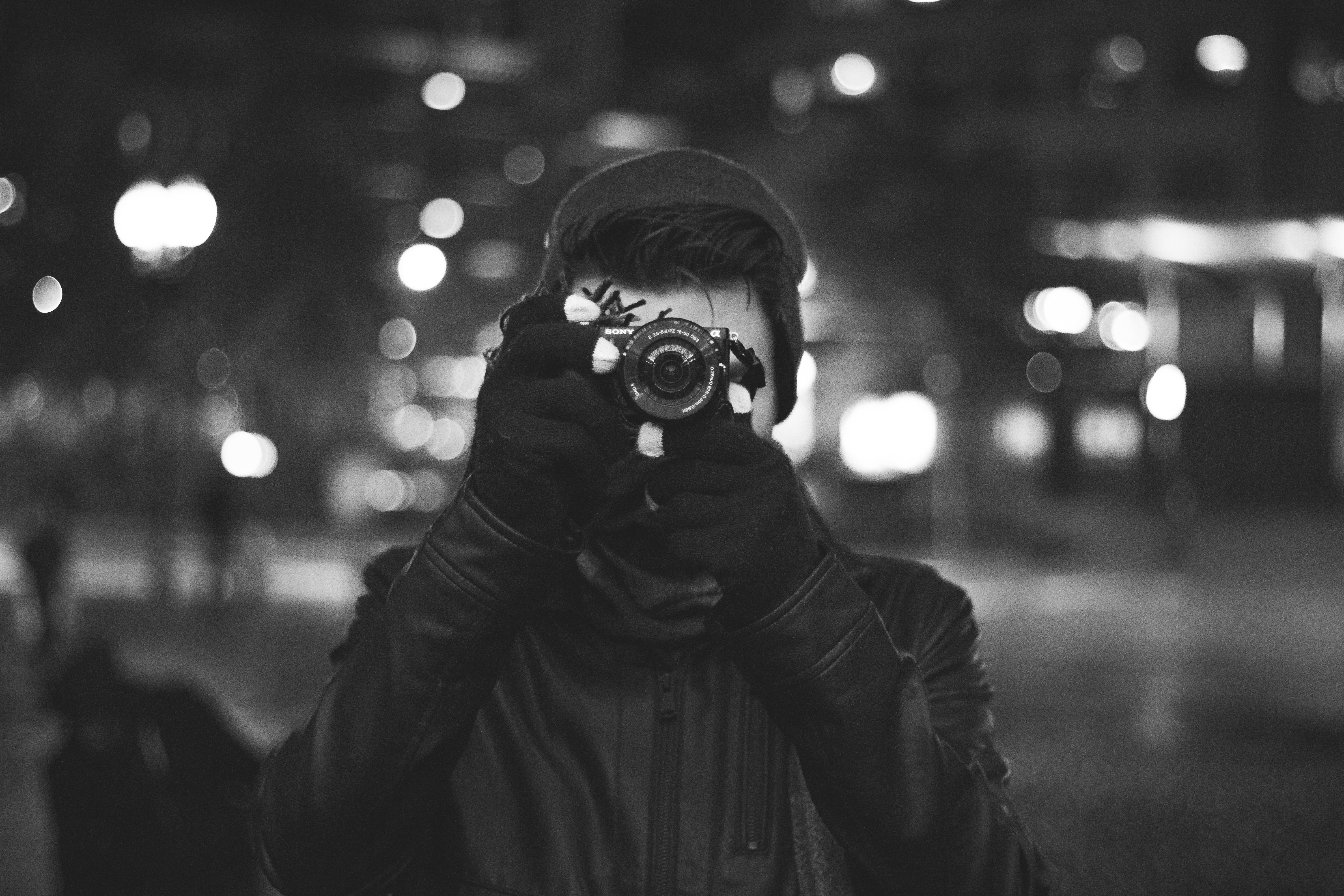 Black and white picture of young man taking photo with gloves, hat and jacket in Boston