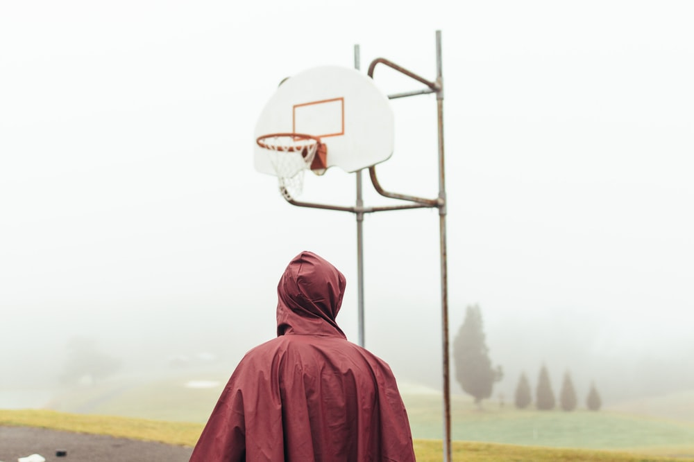 person wearing maroon raincoat standing under white and grey basketball hoop during foggy daytime
