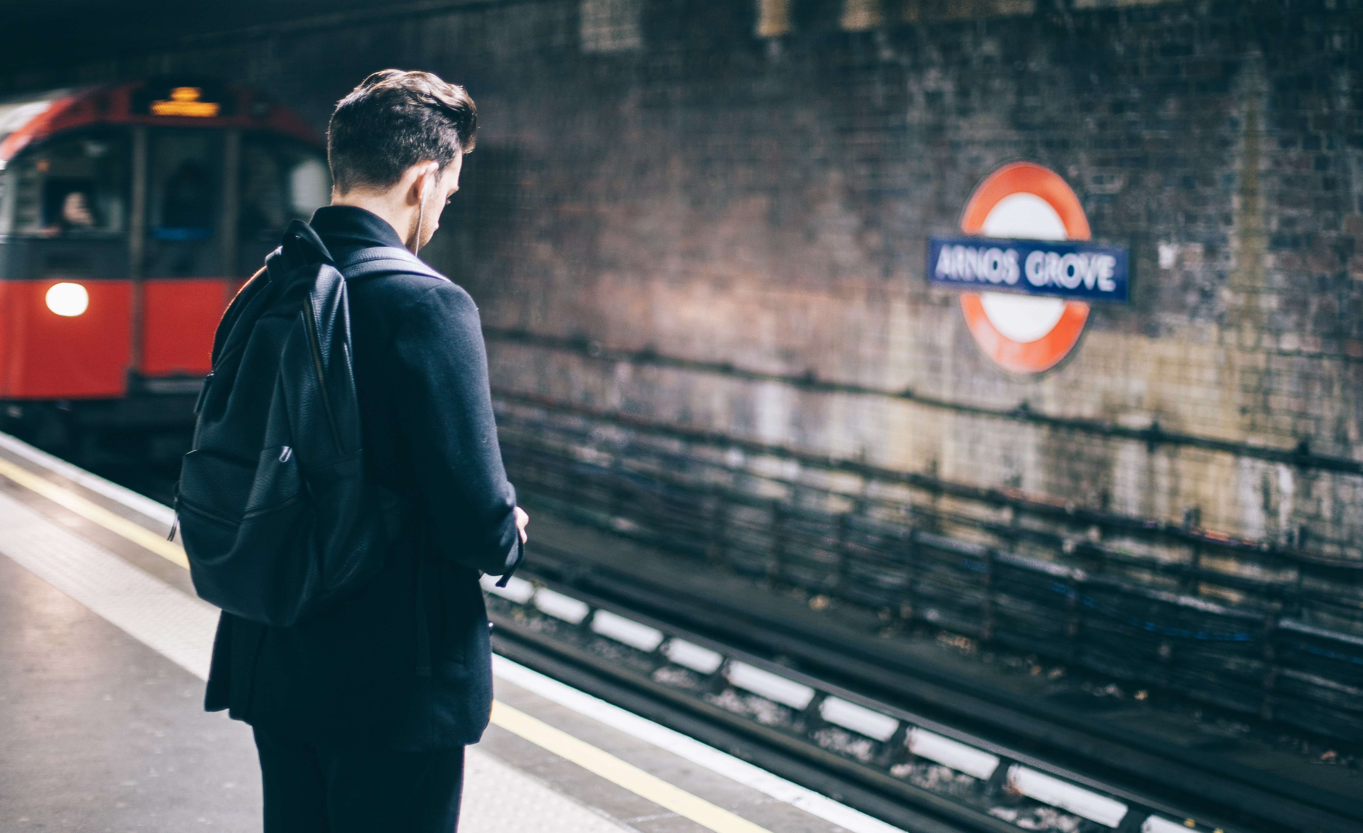 A person waits on a subway platform for an approaching train in Arnos Grove