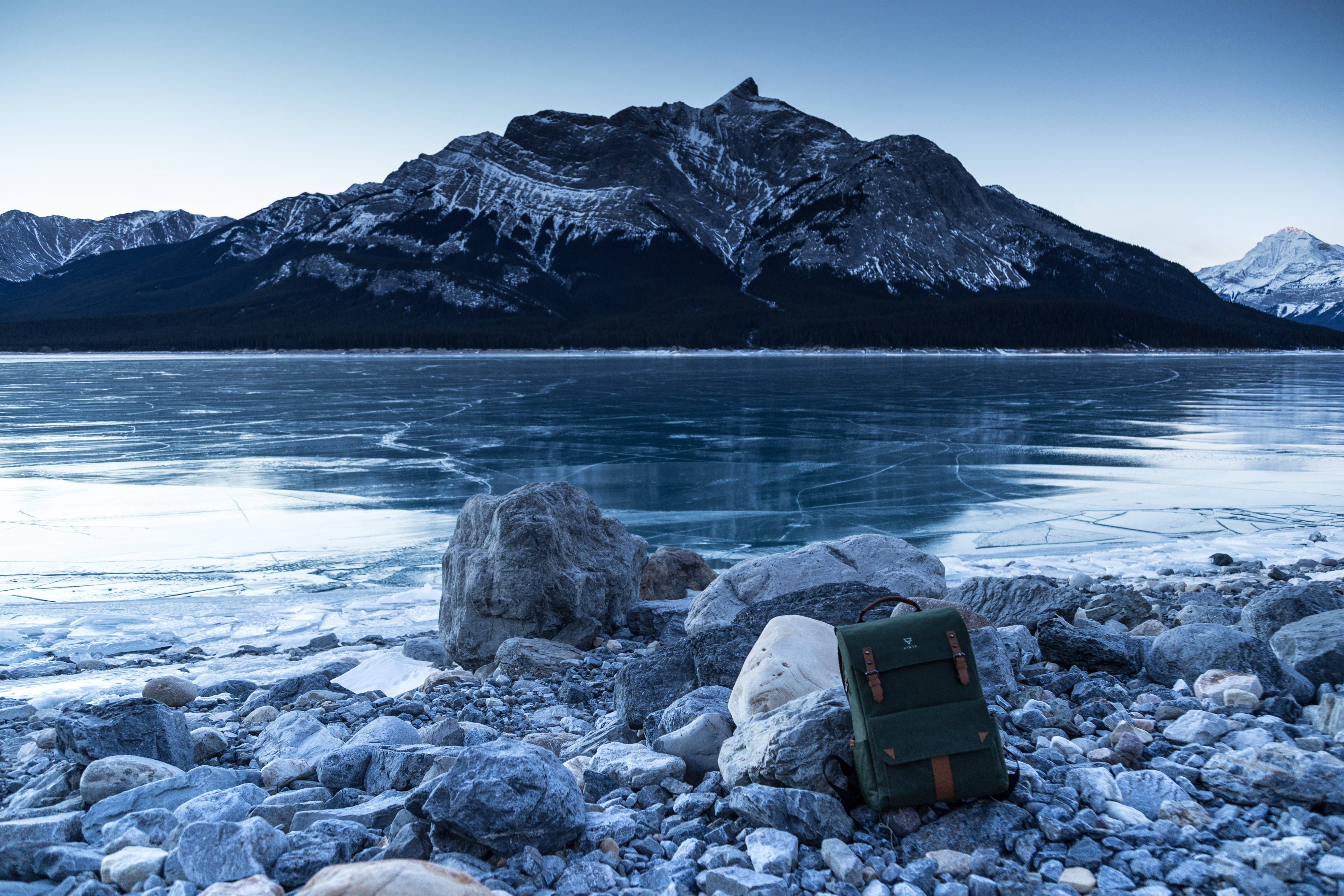 A backpack on rocks on the shore of a frozen lake in Nordegg