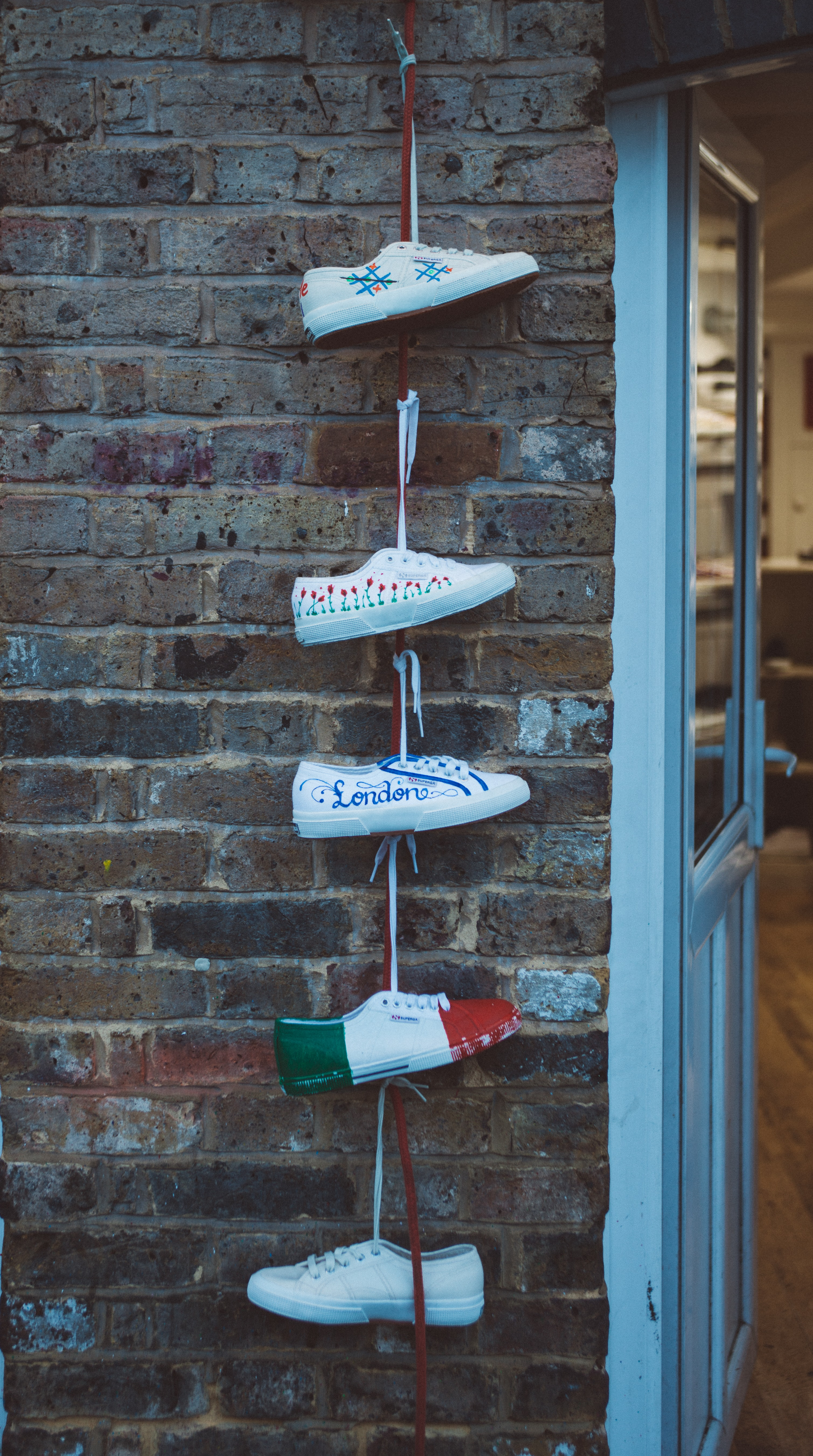 five white sneakers hanged near white door