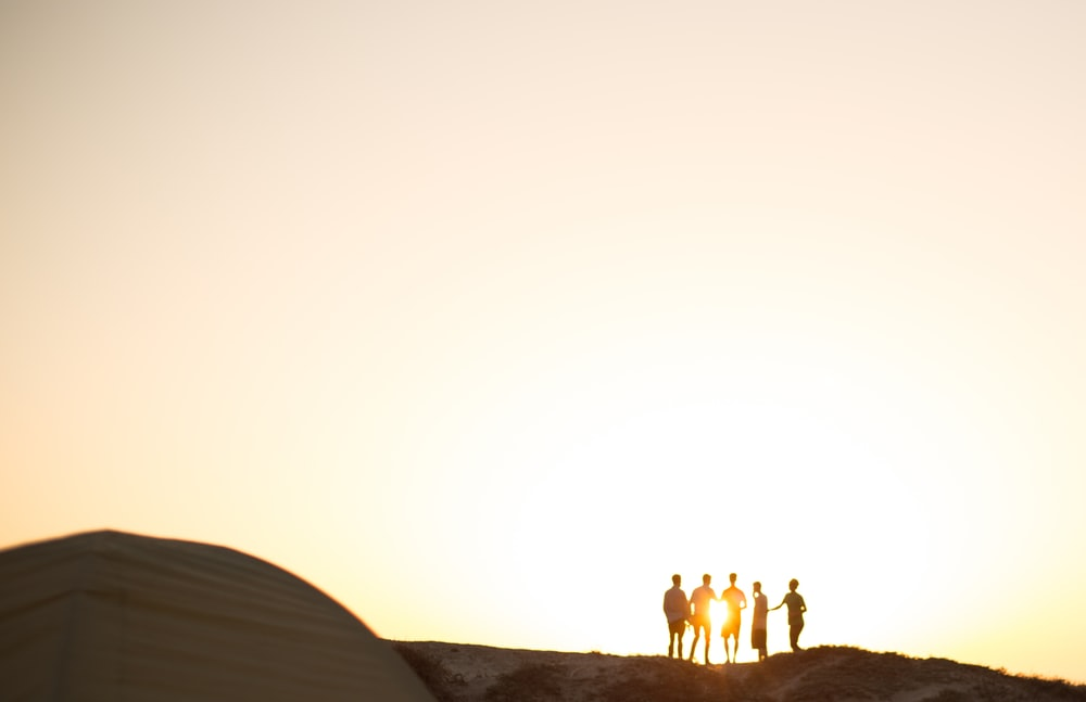 five men standing on a cliff