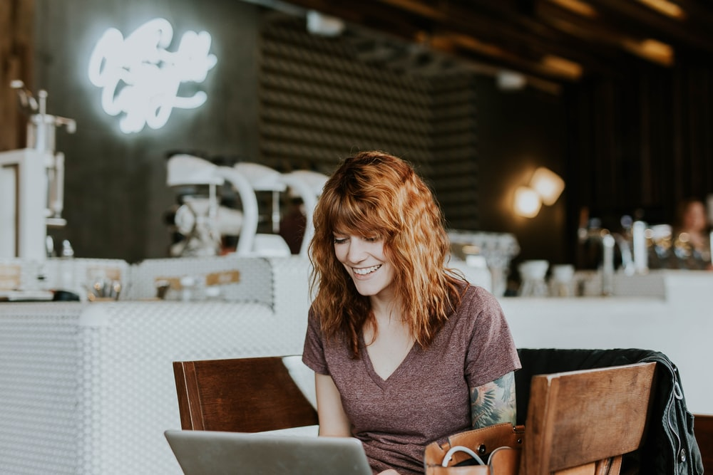 A young woman smiling while looking at a laptop screen at a coffee shop