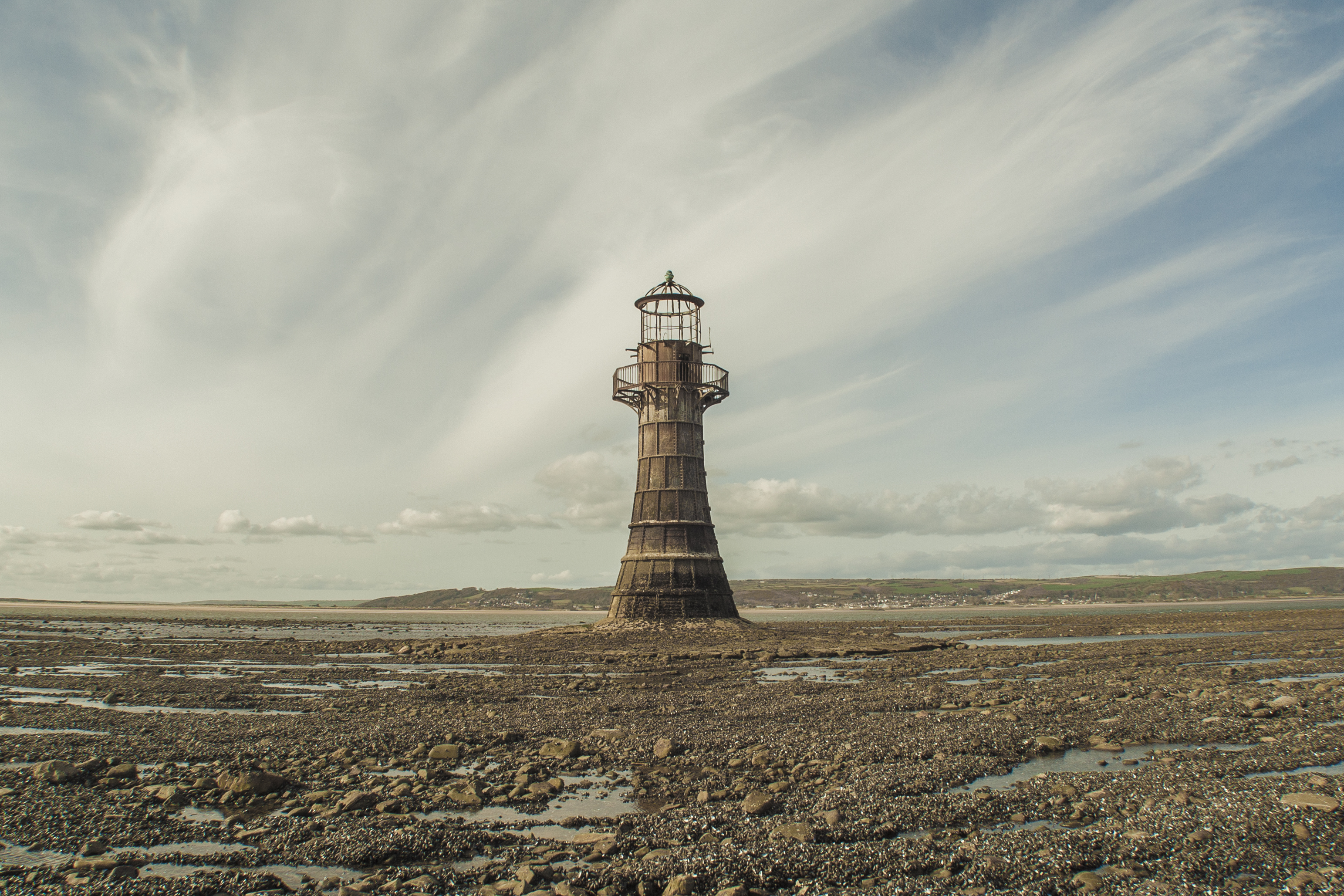 Abandoned lighthouse in Llanmadoc on brown ground against blue sky with clouds