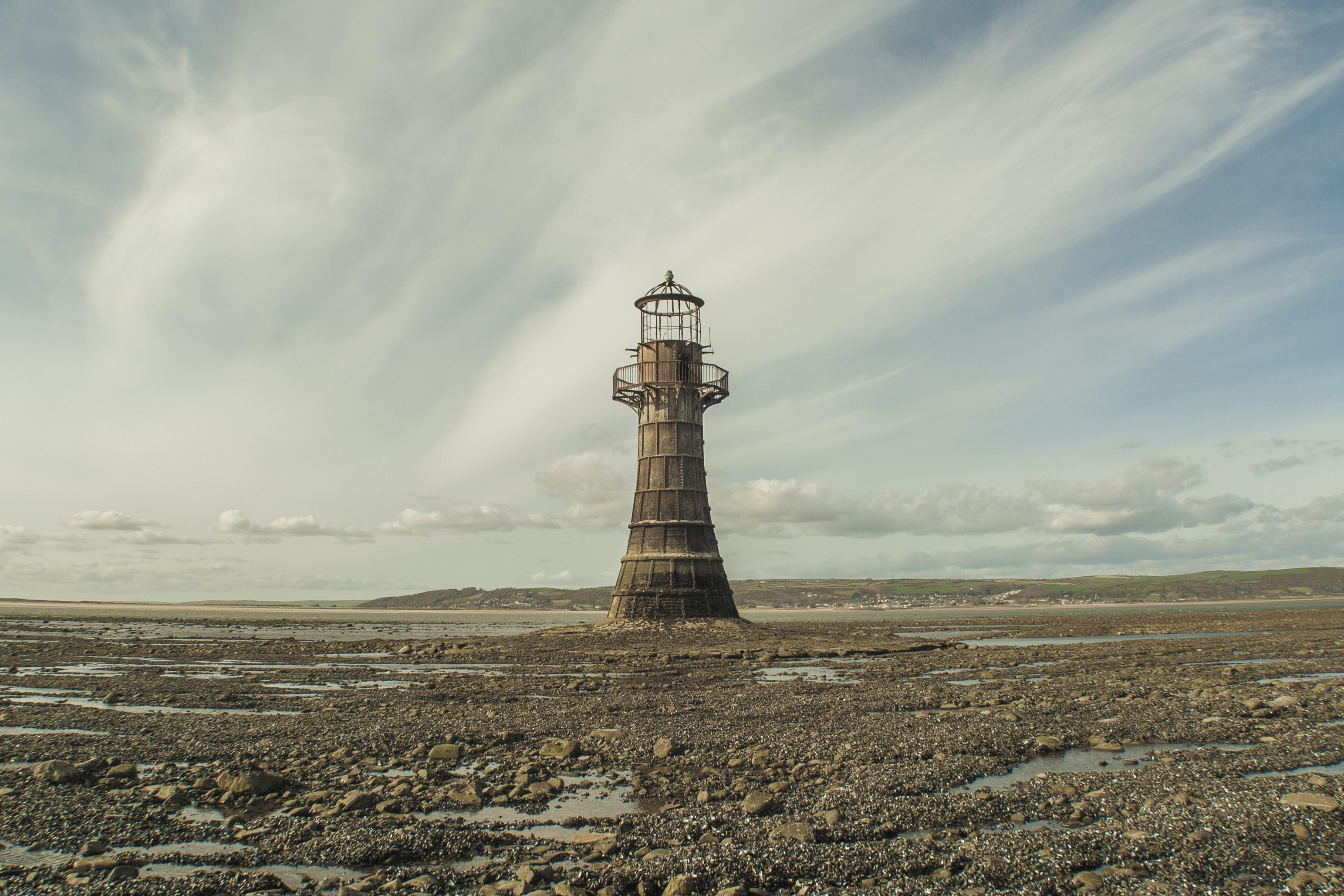 Old abandoned lighthouse on the rocky coast at Llanmadoc