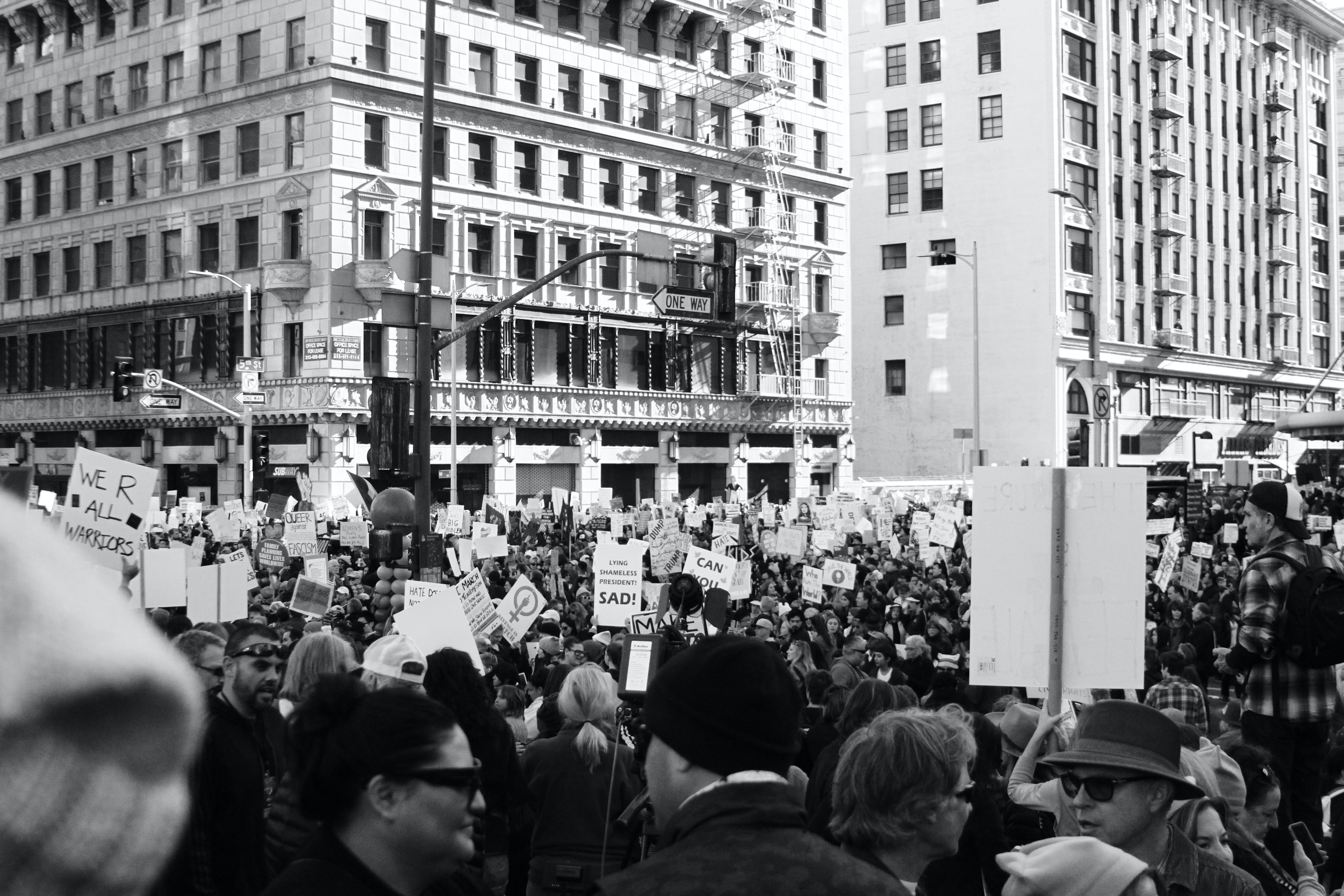 grayscale photography of people protesting in front of concrete building