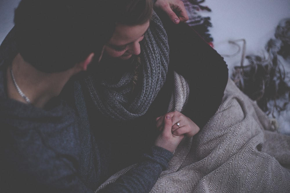 Man and woman snuggle under a blanket, seated and holding hands. She wears an engagement ring.