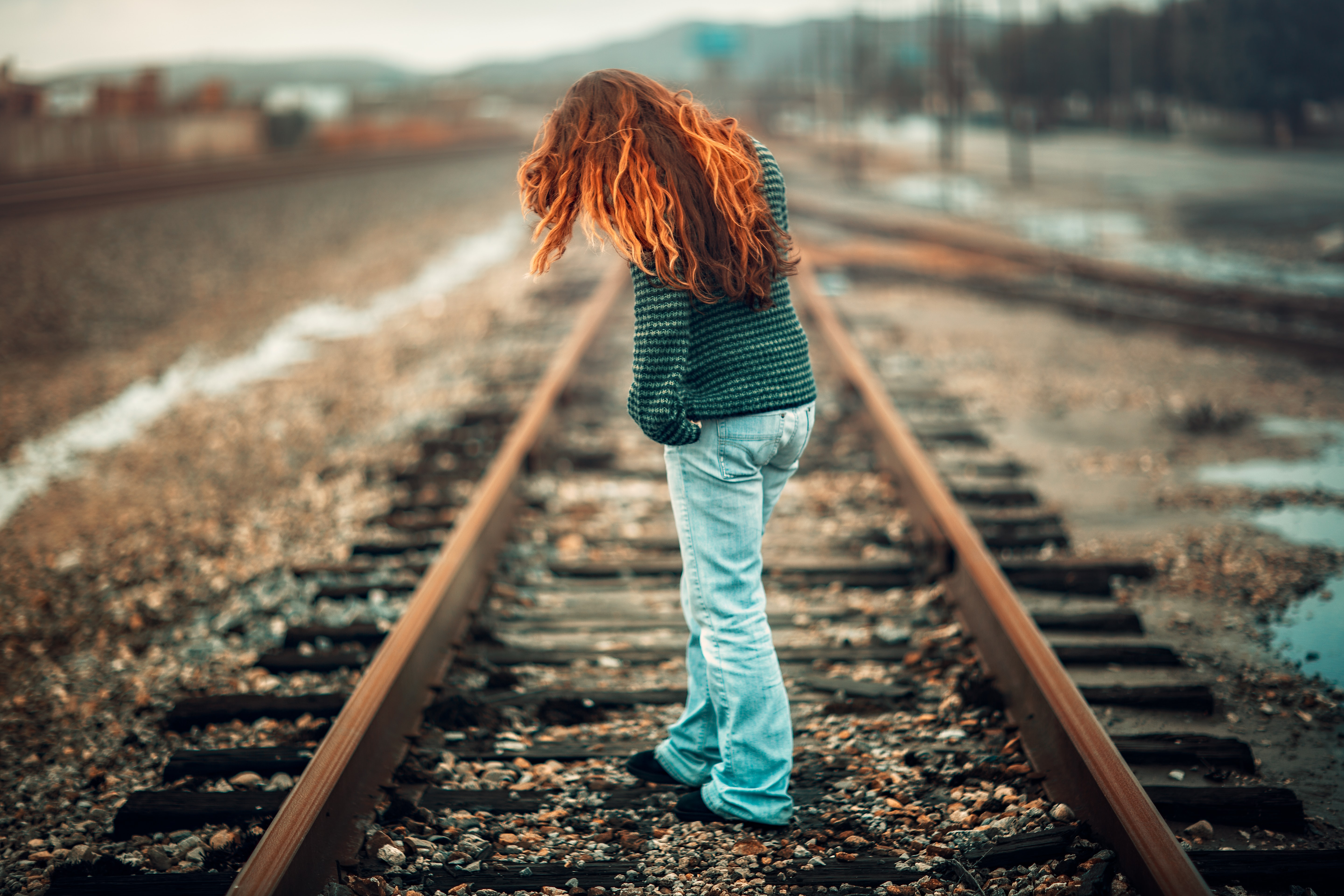 woman with orange hair wearing black and gray stripe long-sleeve shirt and light-blue denim pants standing on train rail at day
