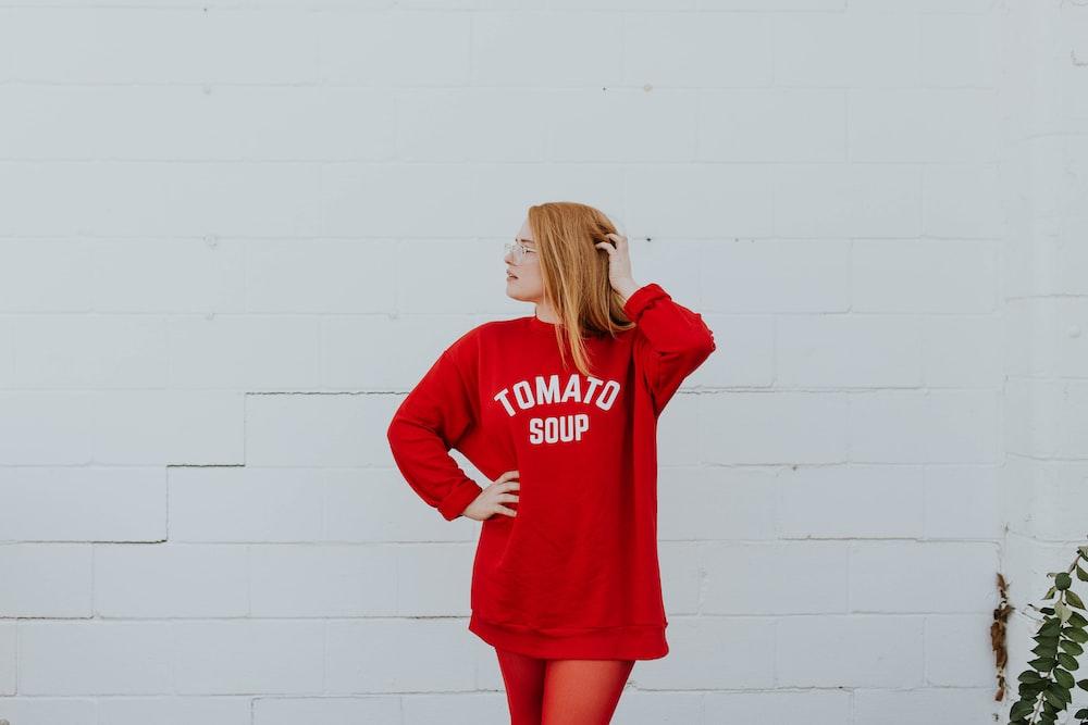 白い塗られた壁の近くに立っている赤い長袖シャツを着ている女性