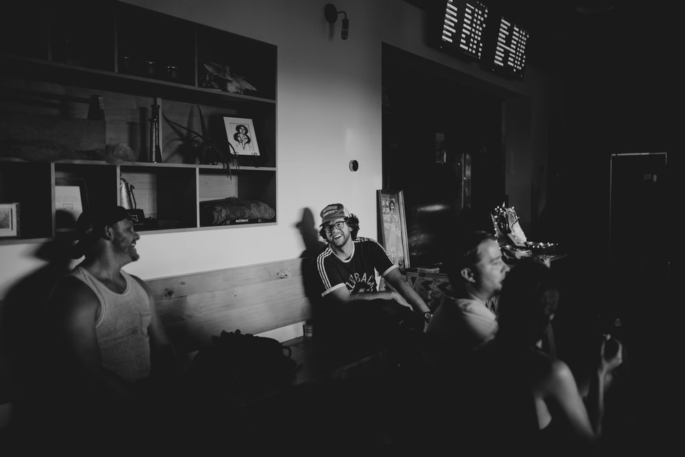 group of people inside the room in grayscale photo