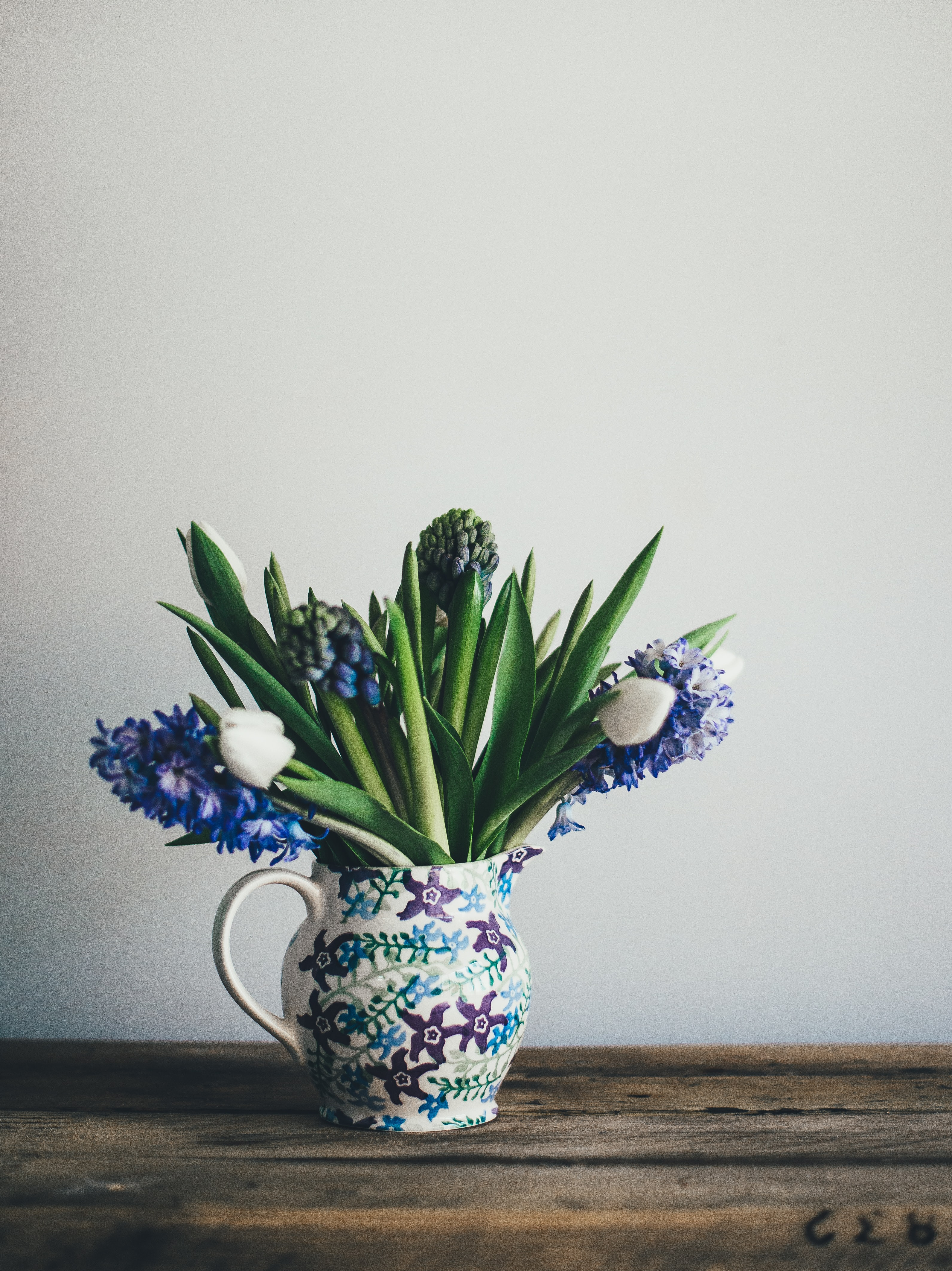 A floral vase with blue hyacinths and white tulips