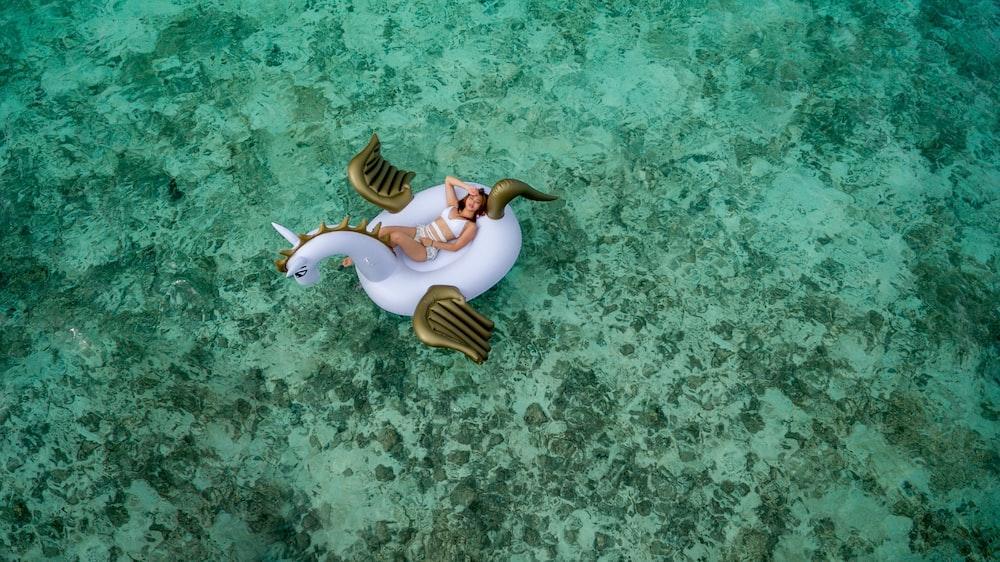 woman wearing white bikini set lying on white and brown unicorn inflatable float