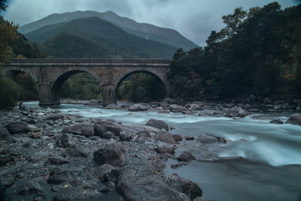 gray arch bridge over river under gray sky at daytime