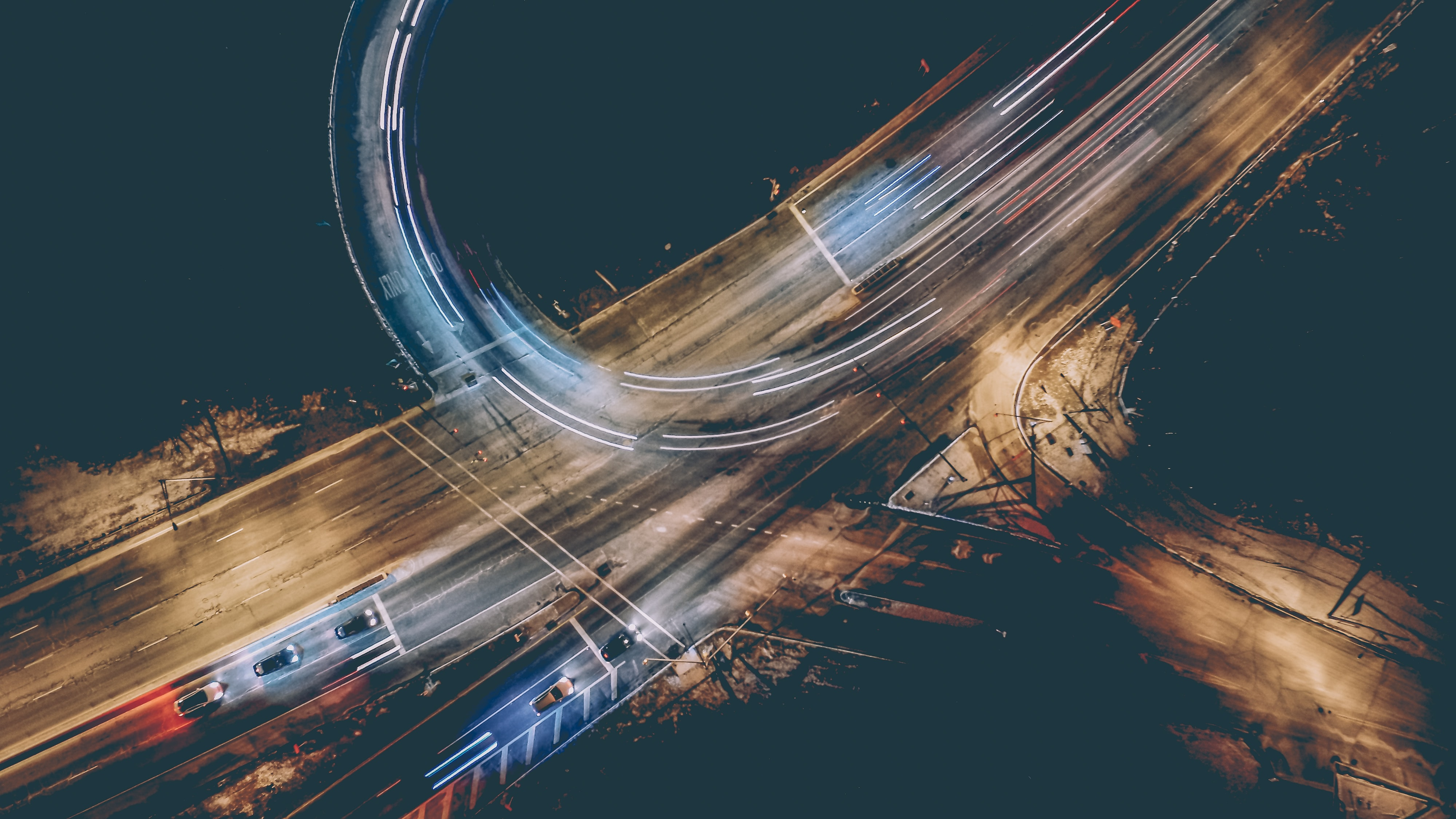 Drone aerial view on a worn down multiple lane intersection with car light trails at night