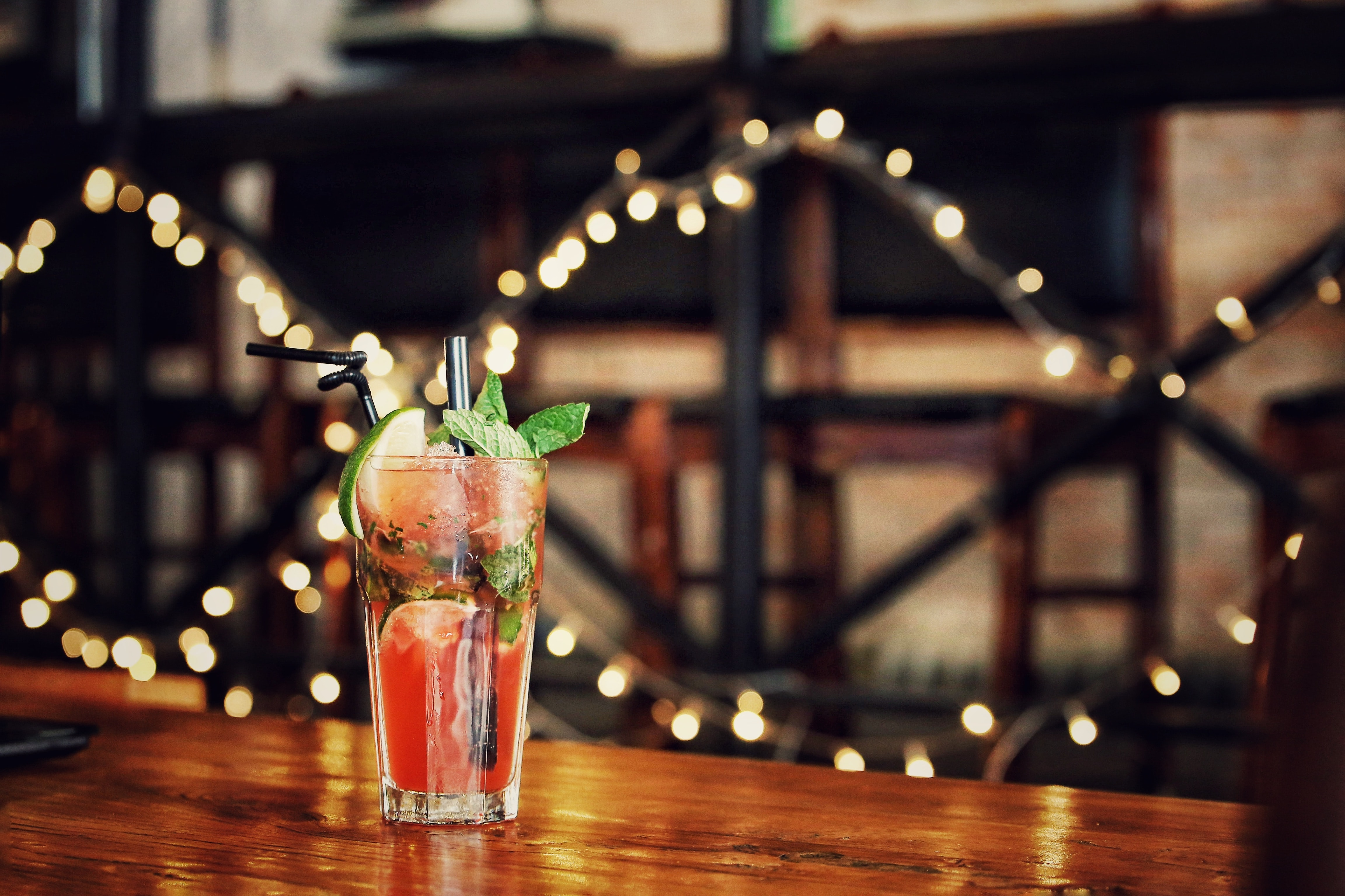 A garnished cocktail beverage with straw and fairy lights behind it