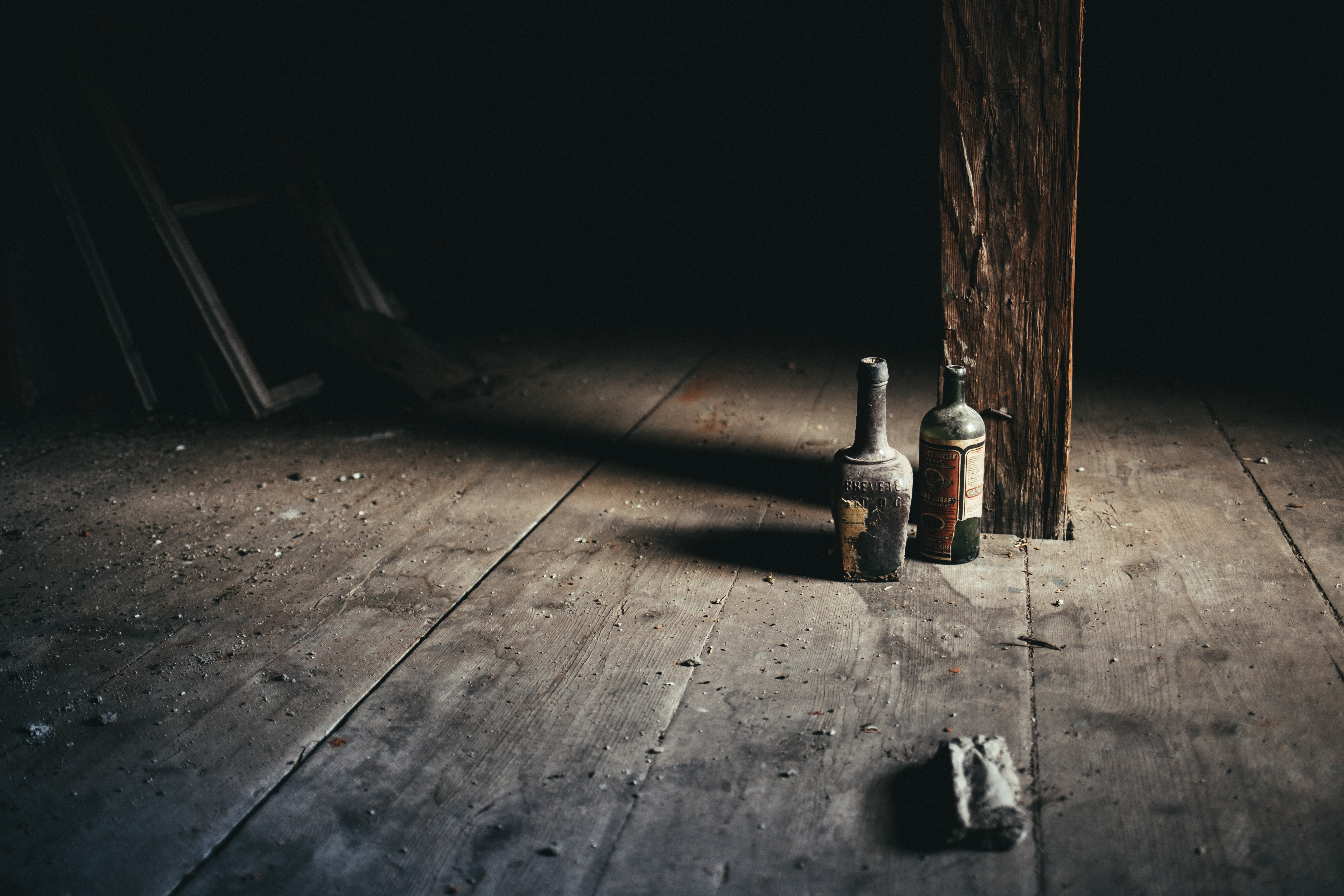 Two old bottles standing on a dusty cabin floor under a wooden post