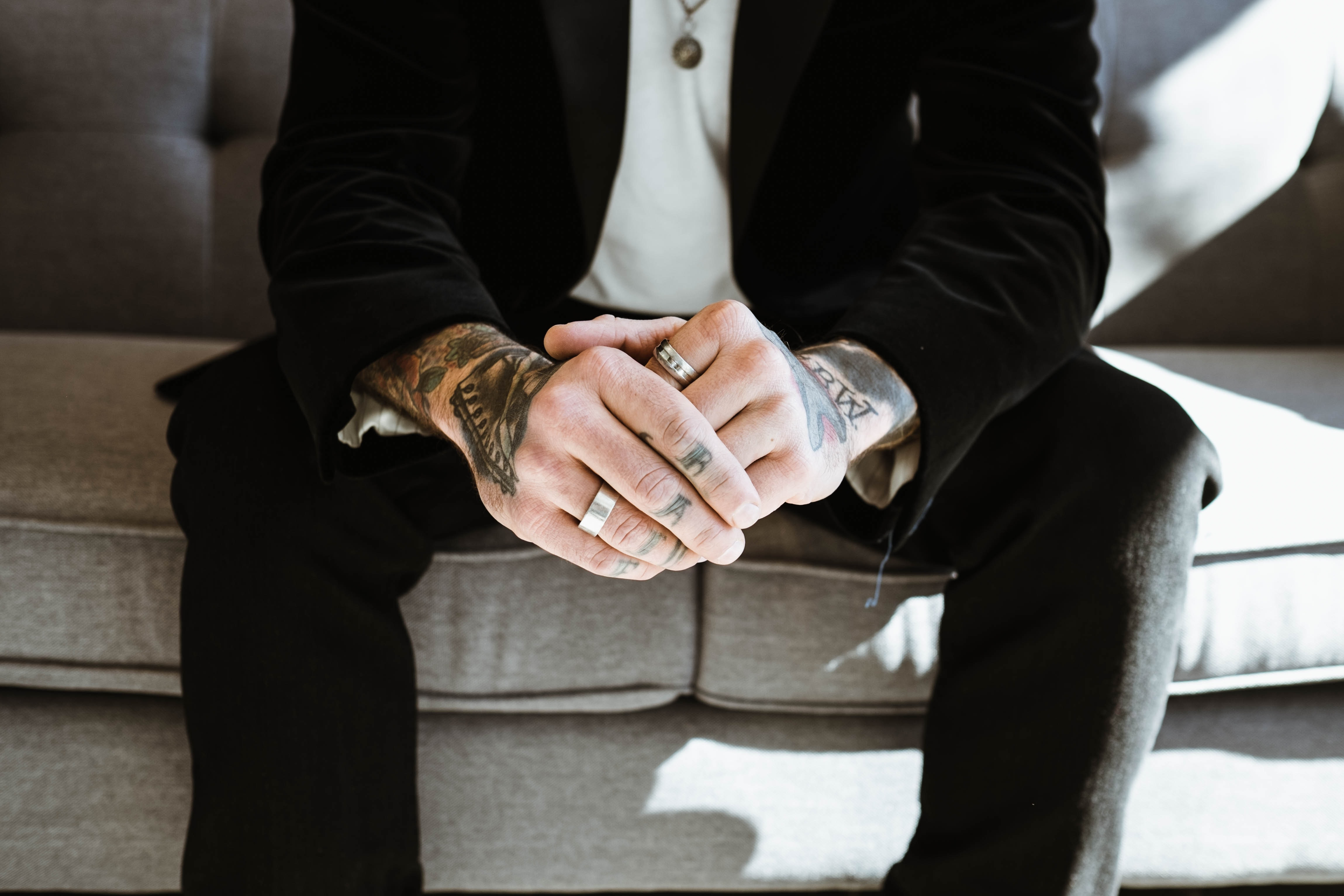 A close-up of a tattooed man's hands in MOD Restaurant & Social.