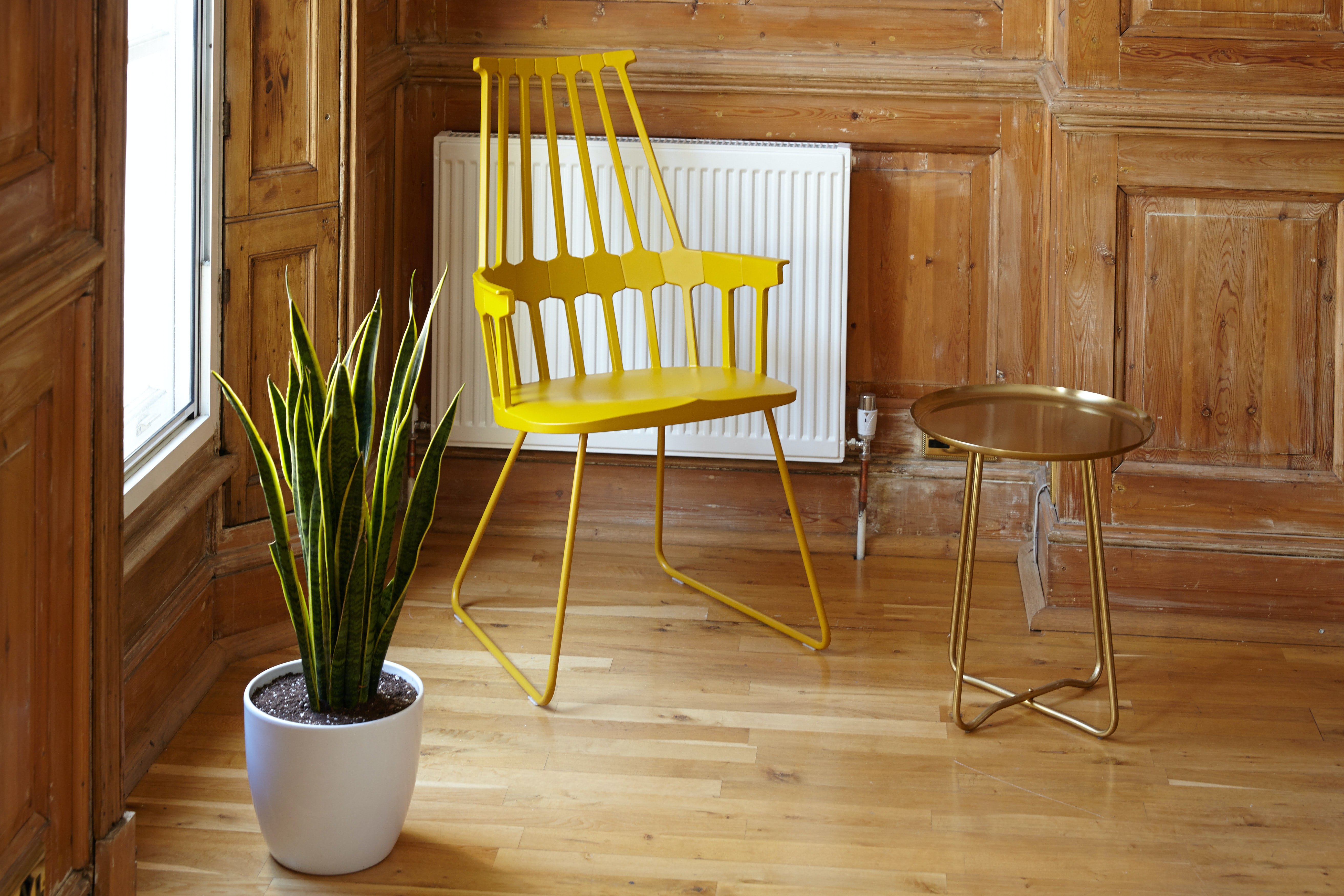 A wooden room with a yellow metal chair, white potted plant, and gold end table in it at 15A Hanover St