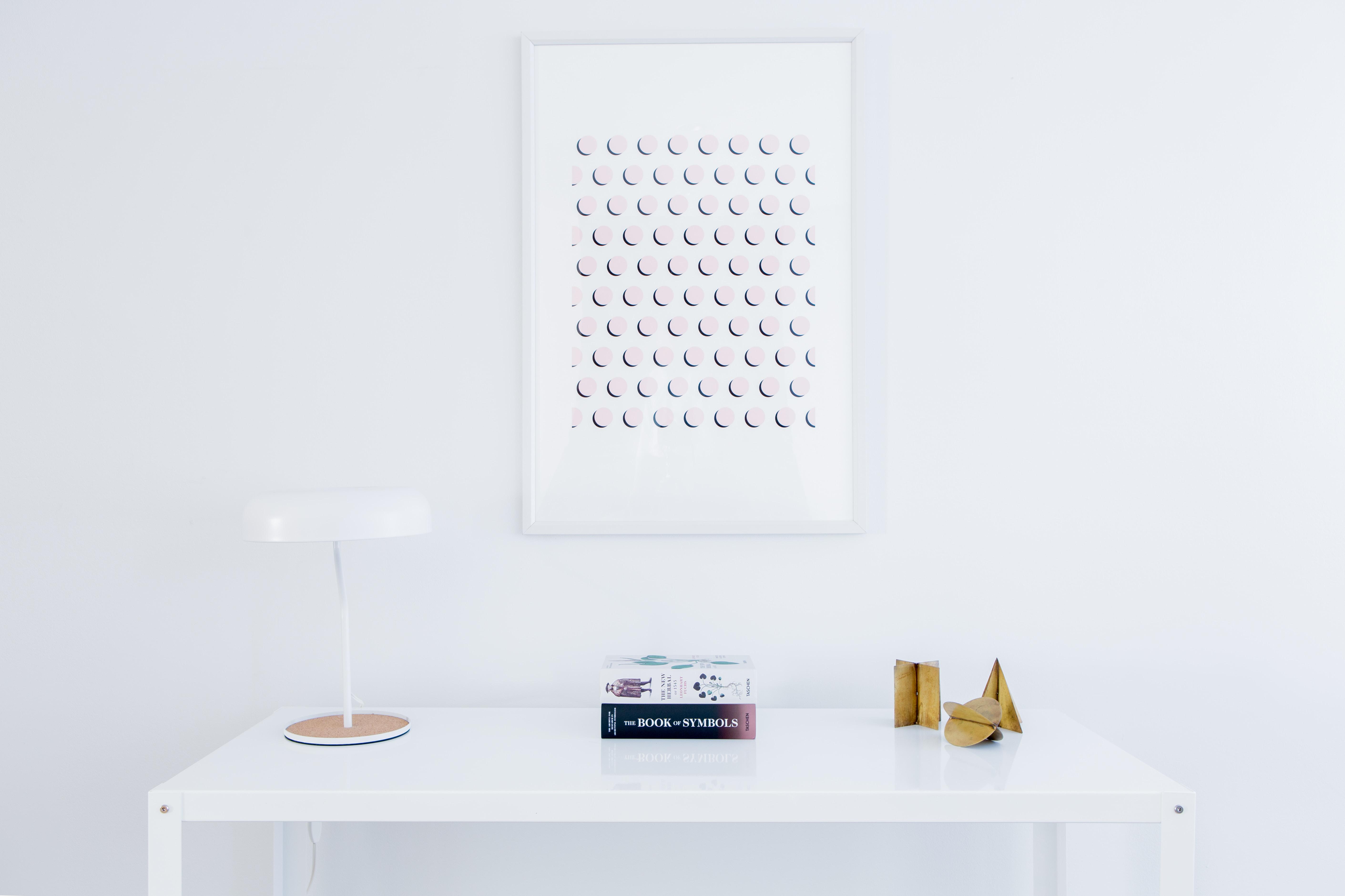 Simple artwork hangs over clean white desk