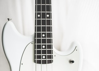 white and black electric bass guitar on white surface