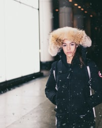 woman in black parka jacket standing while snowing