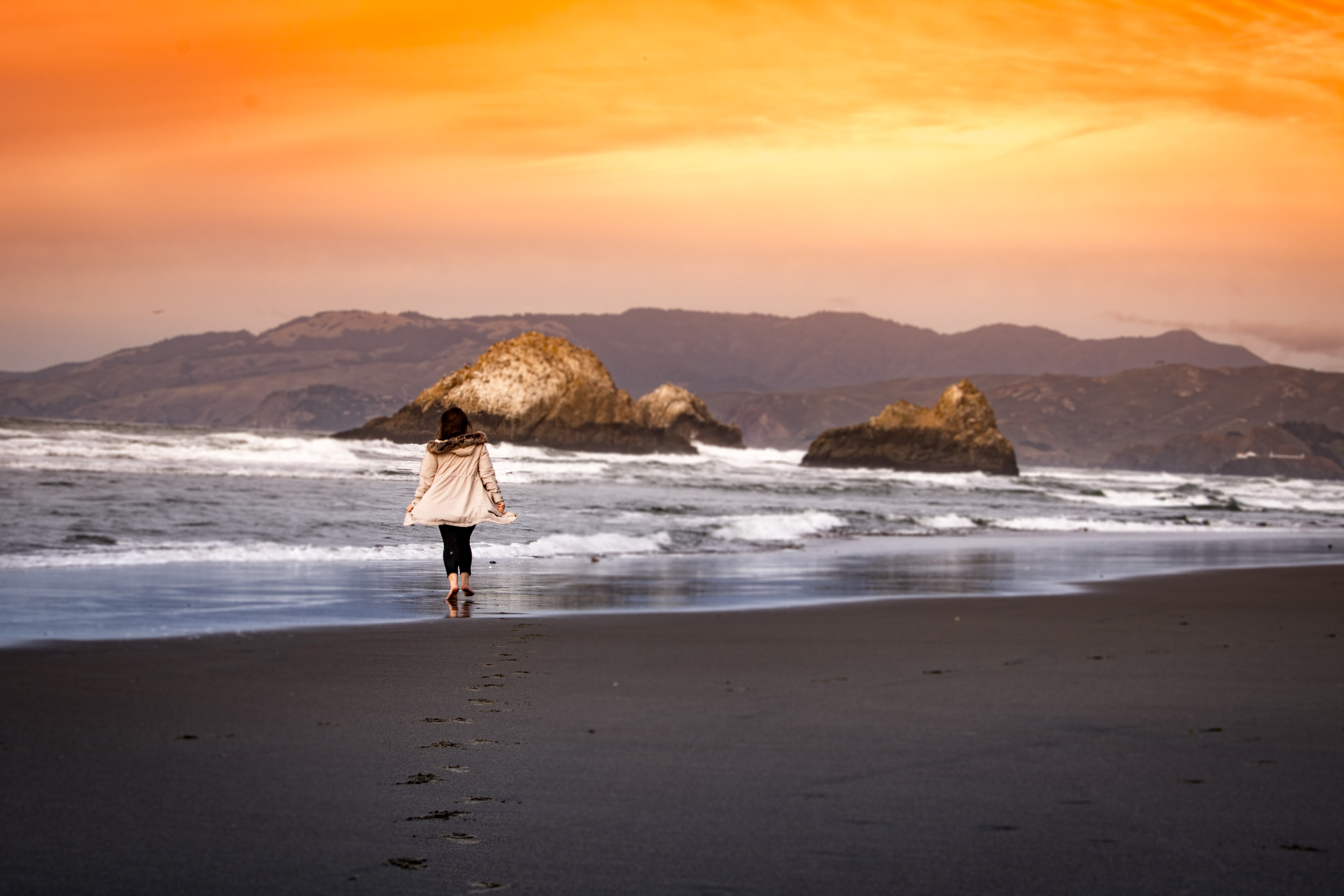 A woman walks across an empty beach as ocean waves crash on to the rocks and the sun sets in the sky