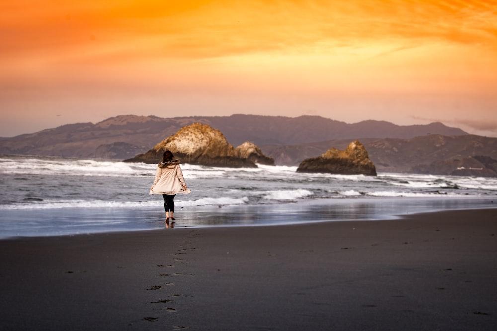 woman wearing on seashore during sunset