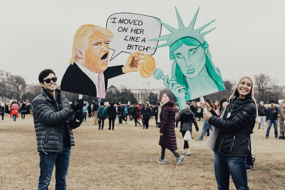 person wearing black bubble jacket holding donald trump signage