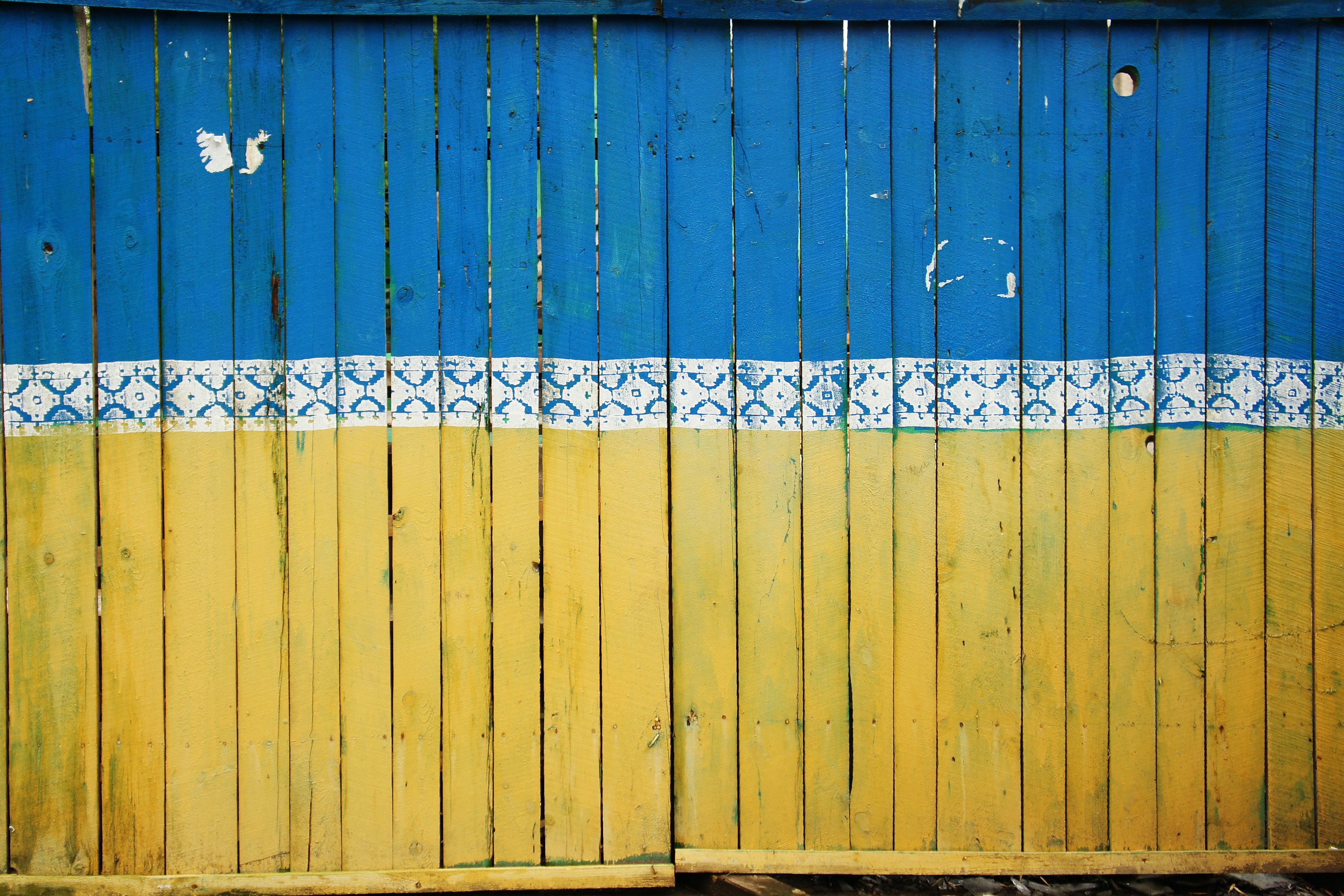 A tall wooden fence painted blue and yellow with a white folk pattern in the middle