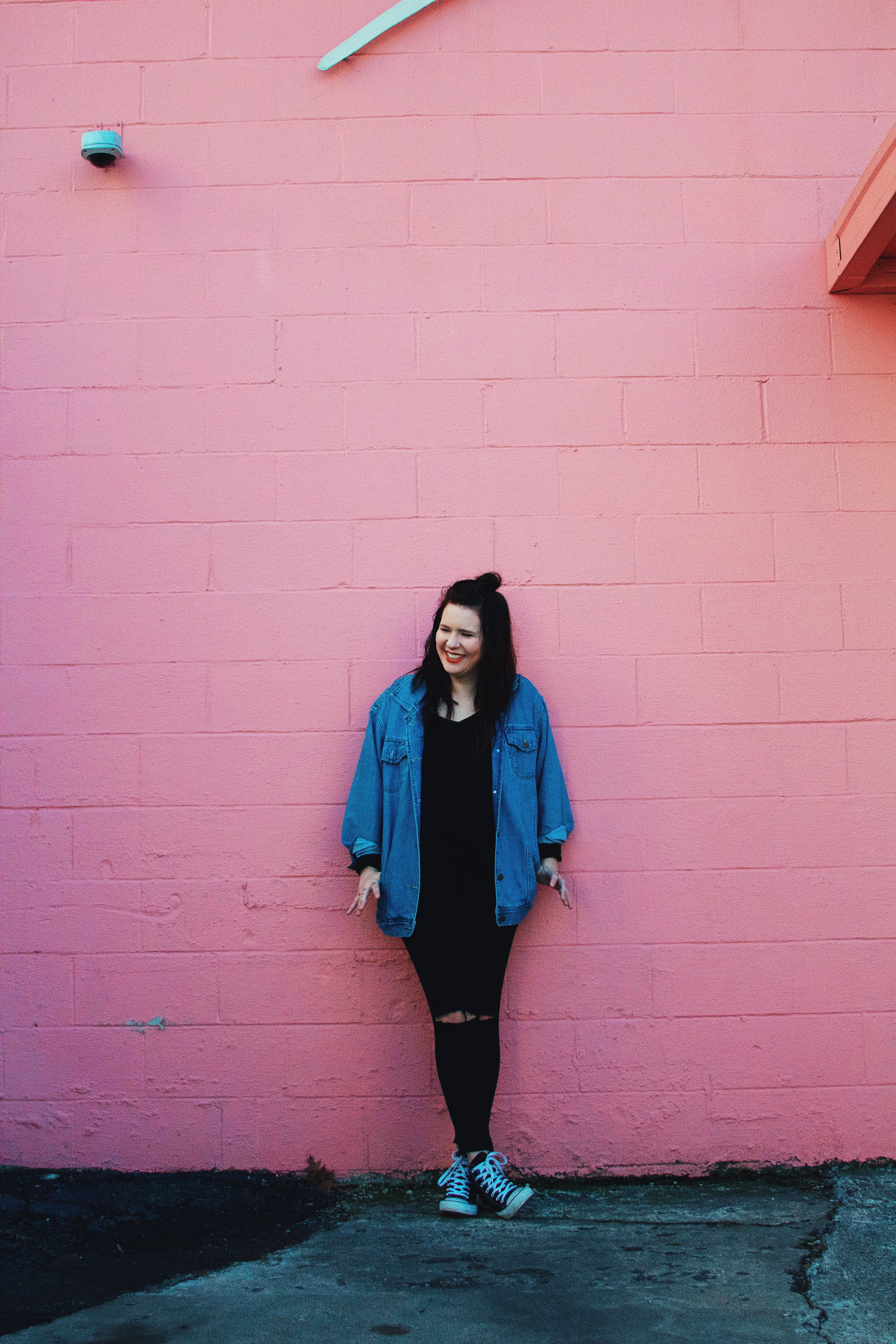A smiling woman in a denim jacket and ripped jeans leaning against a pink wall
