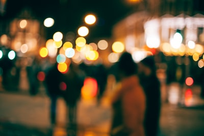 an out-of-focus look at people walking outside in a town at night with with blurs of dotted light all around blurred zoom background