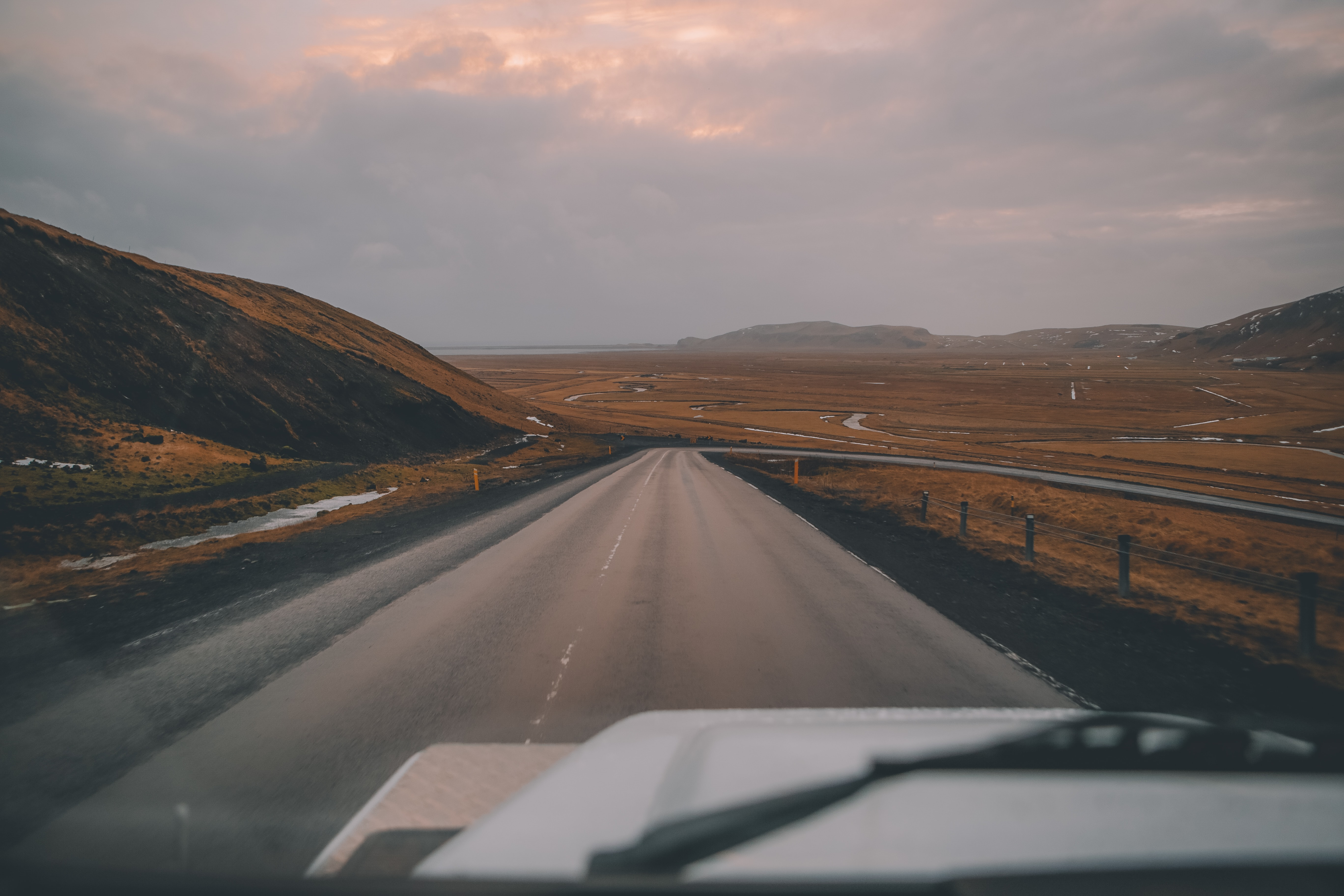 The view from the windshield on an empty road through cold Icelandic plains
